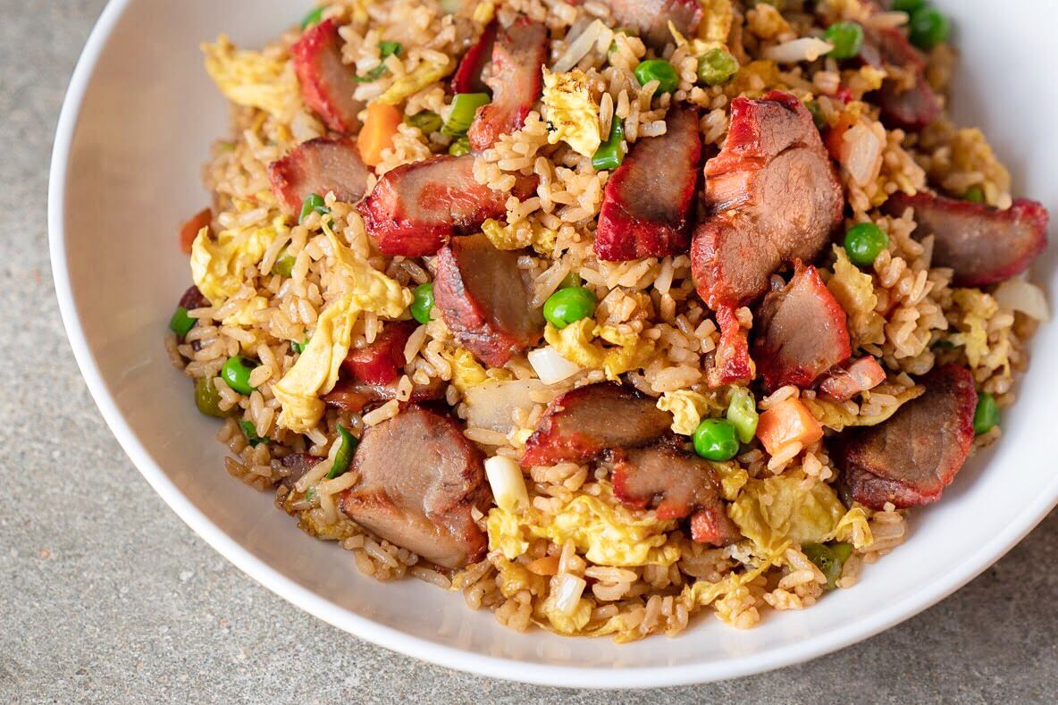 A shallow white bowl filled with fried rice, green peas, and chunks of barbecue pork, along with other vegetables, that is placed on a light gray table