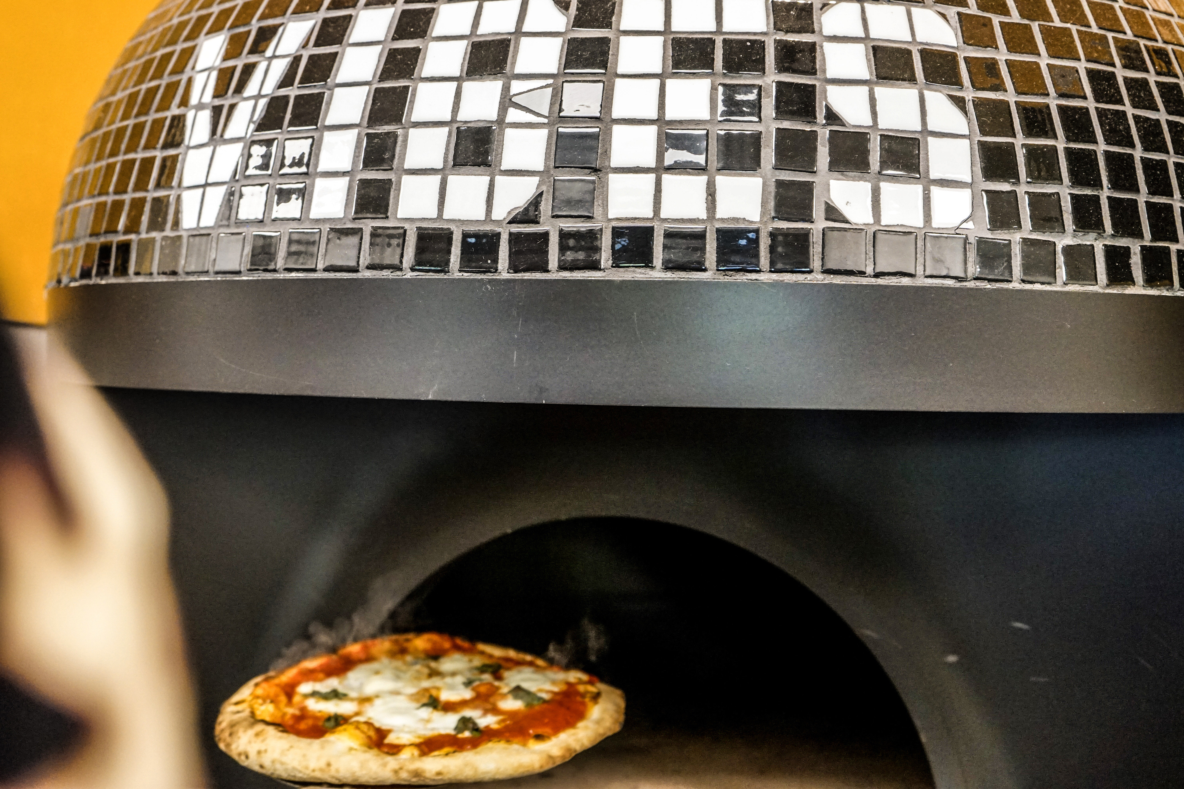 """Black tiled dome of the wood-fire pizza oven at Holmes Slice with white tiles spelling out """"Vibes"""", a margherita pizza is coming out of the oven"""