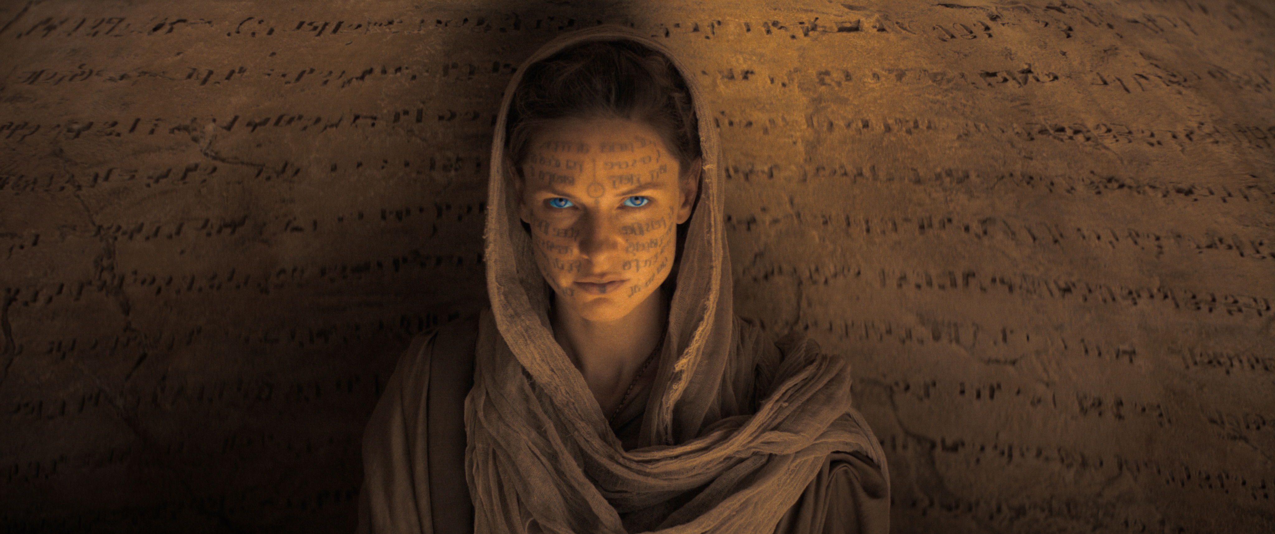 Rebecca Ferguson, in sandy robes, sits in front of a wall carved with lines of alien text. Her face is also scrawled with alien text, and her eyes are glowing blue in Dune.