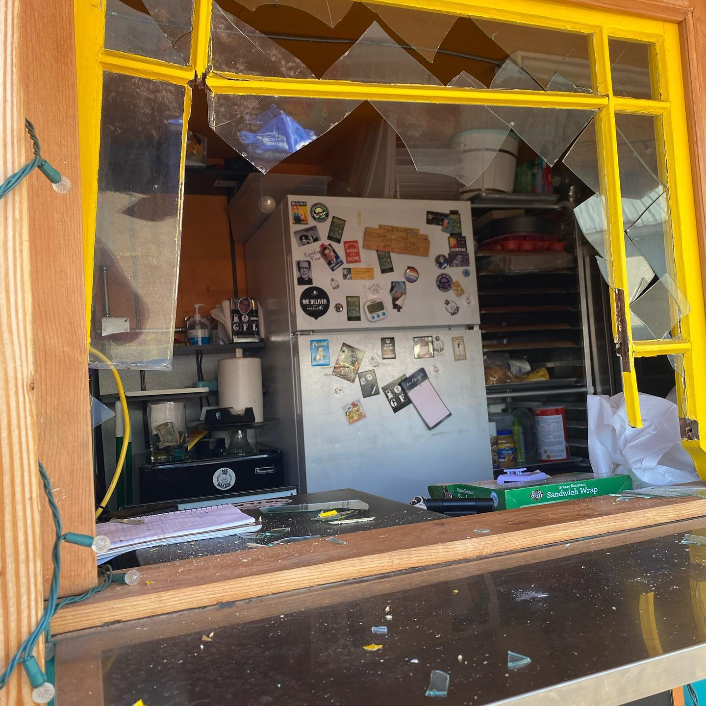 A broken window reveals a burglarized kitchen within the food cart We Are Baked