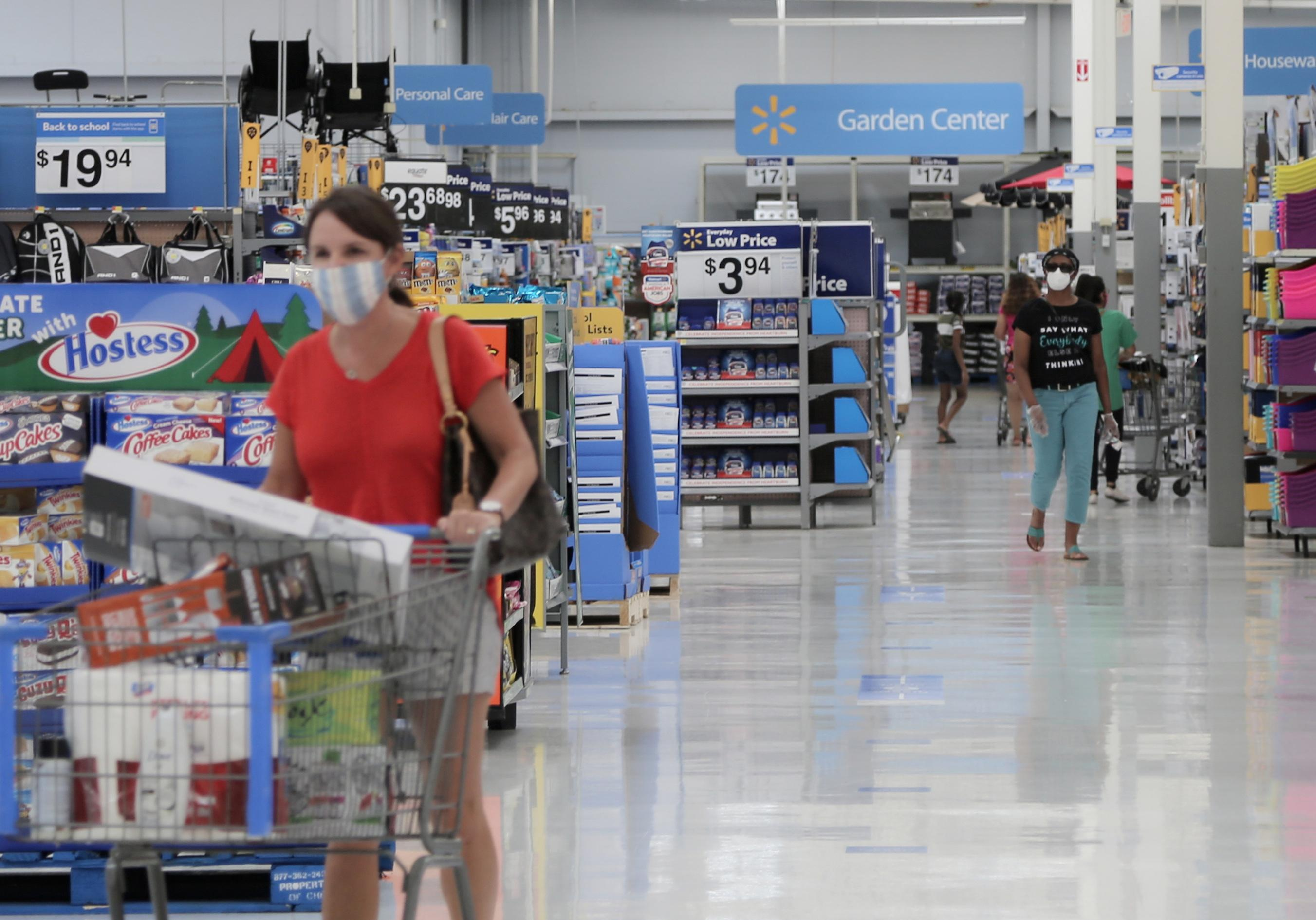 The interior of a Walmart store with a customer pushing a shopping cart down the aisle.