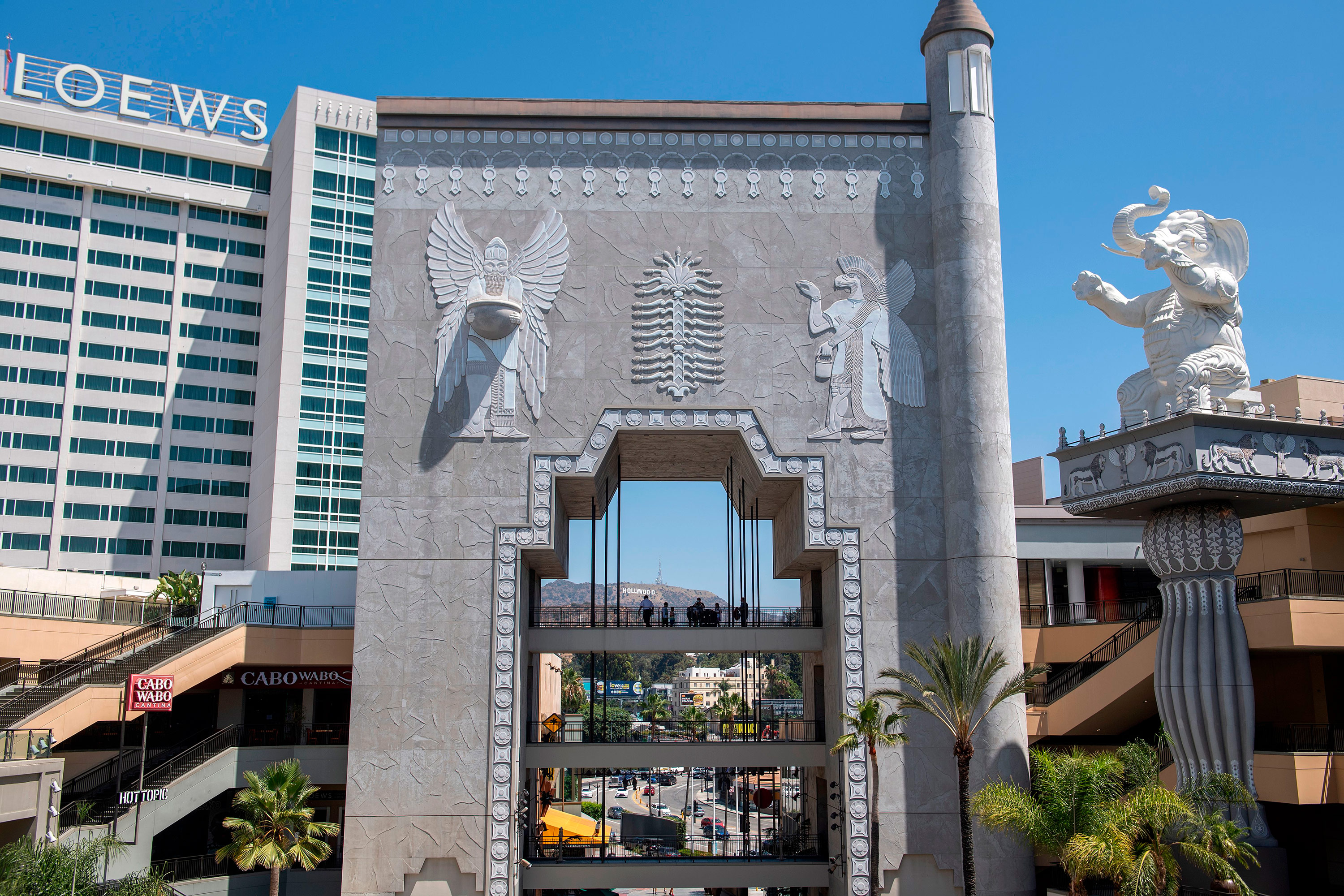 An elephant topped column and an arch with Babylonian images framing the Hollywood sign in the distance are seen inside the Hollywood & Highland shopping center on August 7 2020, in Hollywood, California. The racist statues were built to honor D.W. Griffith's 1916 film Intolerance.