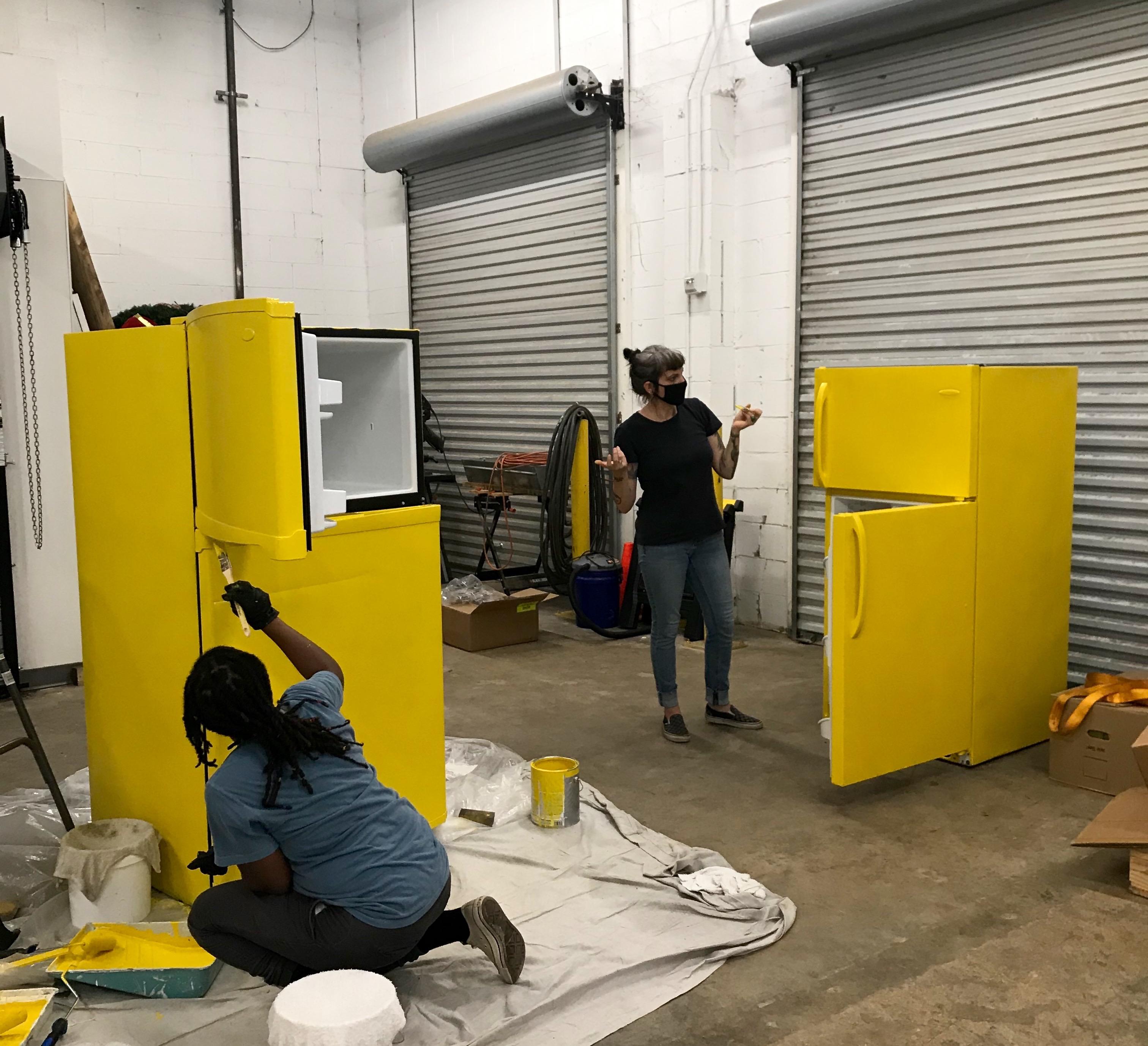 两名志愿者,一名非裔美国妇女跪在左边,一名白人妇女站在右边,两人都戴着面具,在一个白色的大车库中将捐赠的两个冰箱涂成黄色