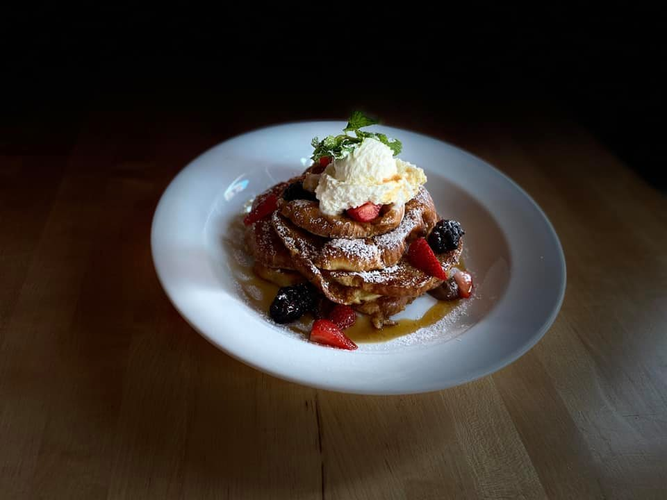 plate of french toast with berries and cream