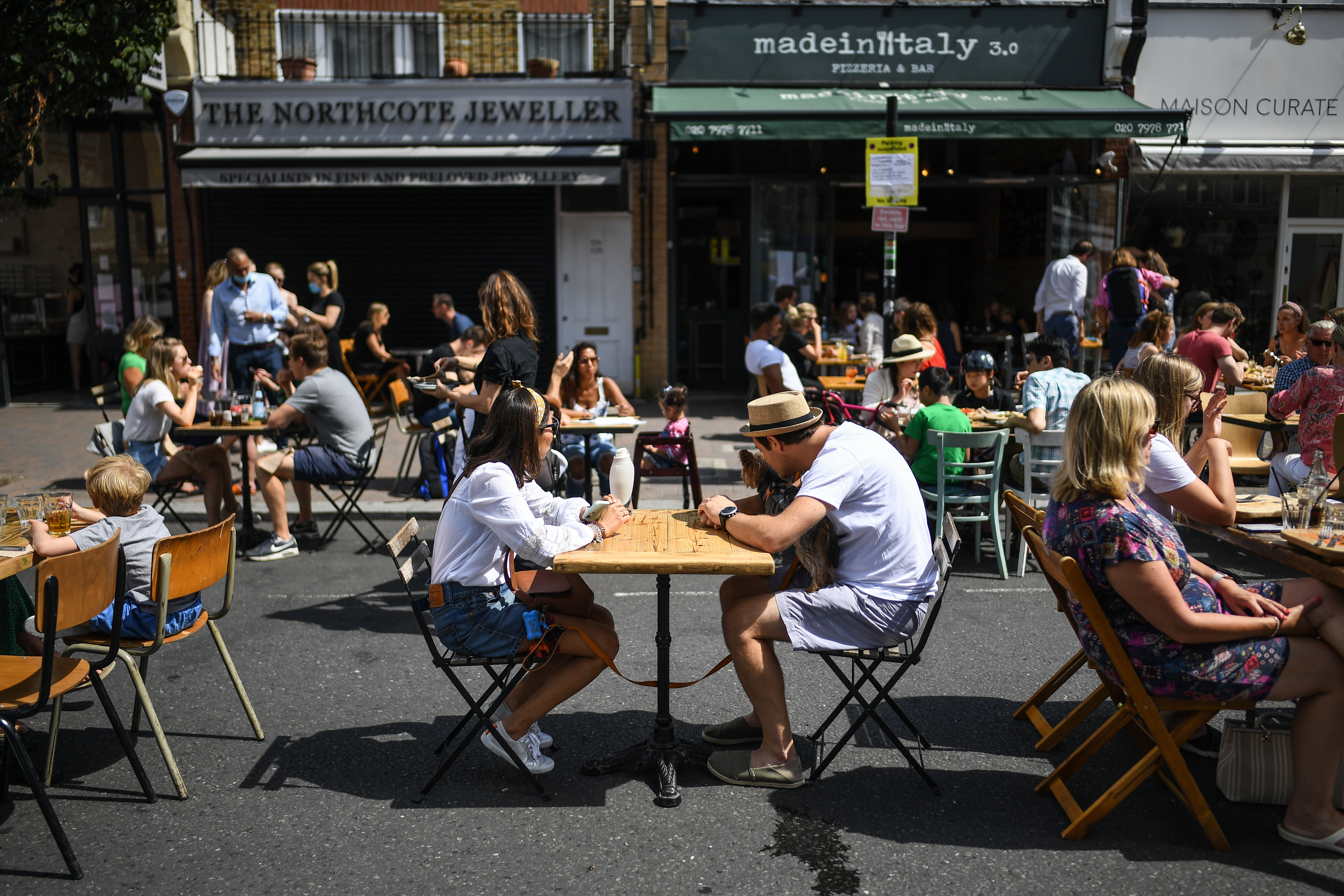 Diners sit outside at tables on a street in Clapham, London