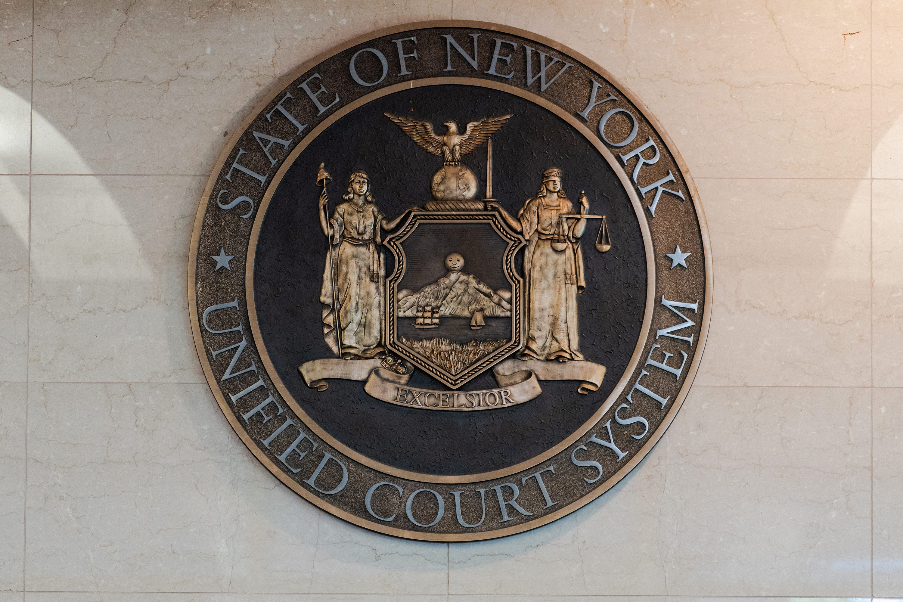 The seal of the State of New York Unified Court System hangs in the lobby of Kings County Supreme Court.