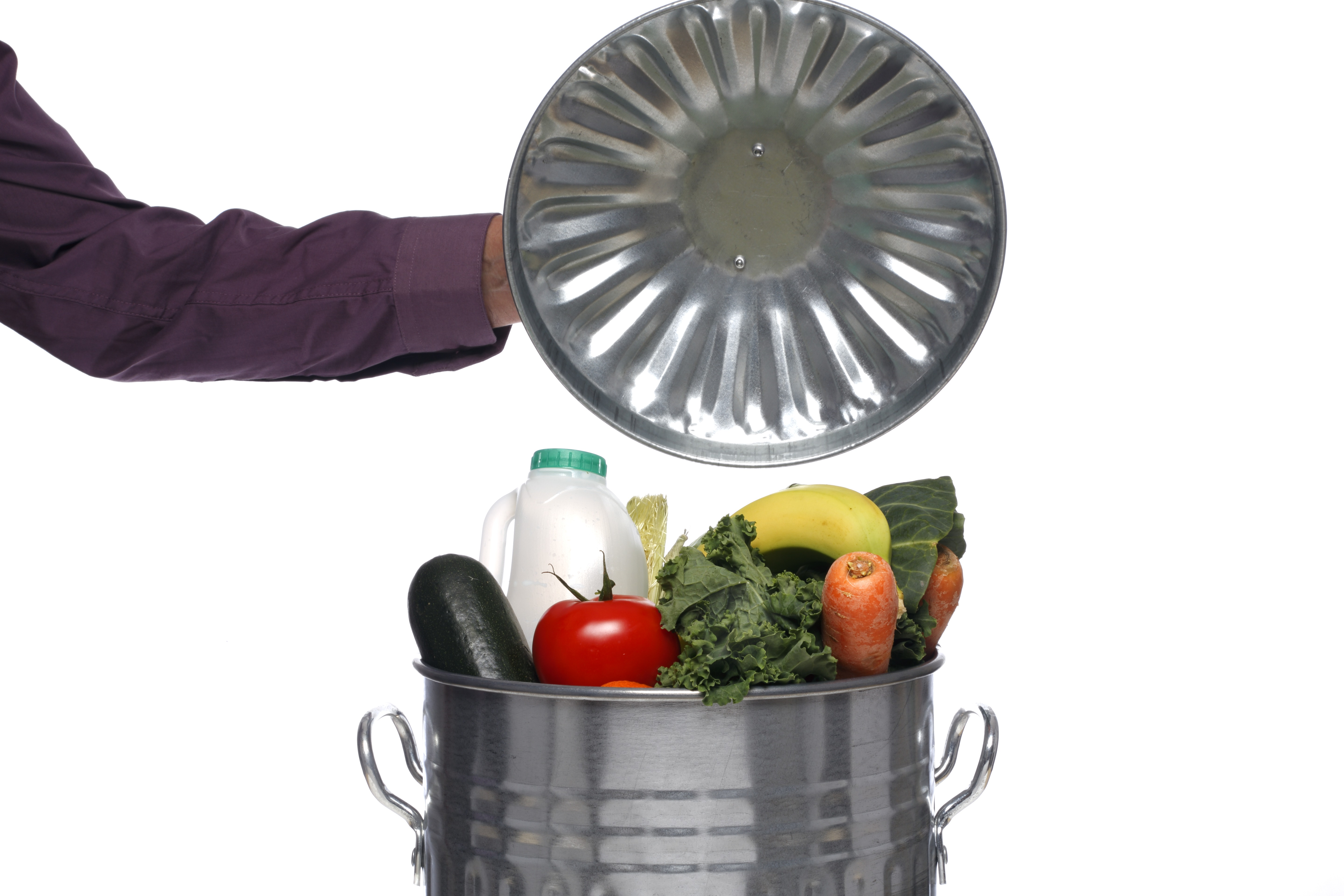 A trash can lid is held open to reveal fresh fruits and vegetables and a container of milk sitting in the trash can.