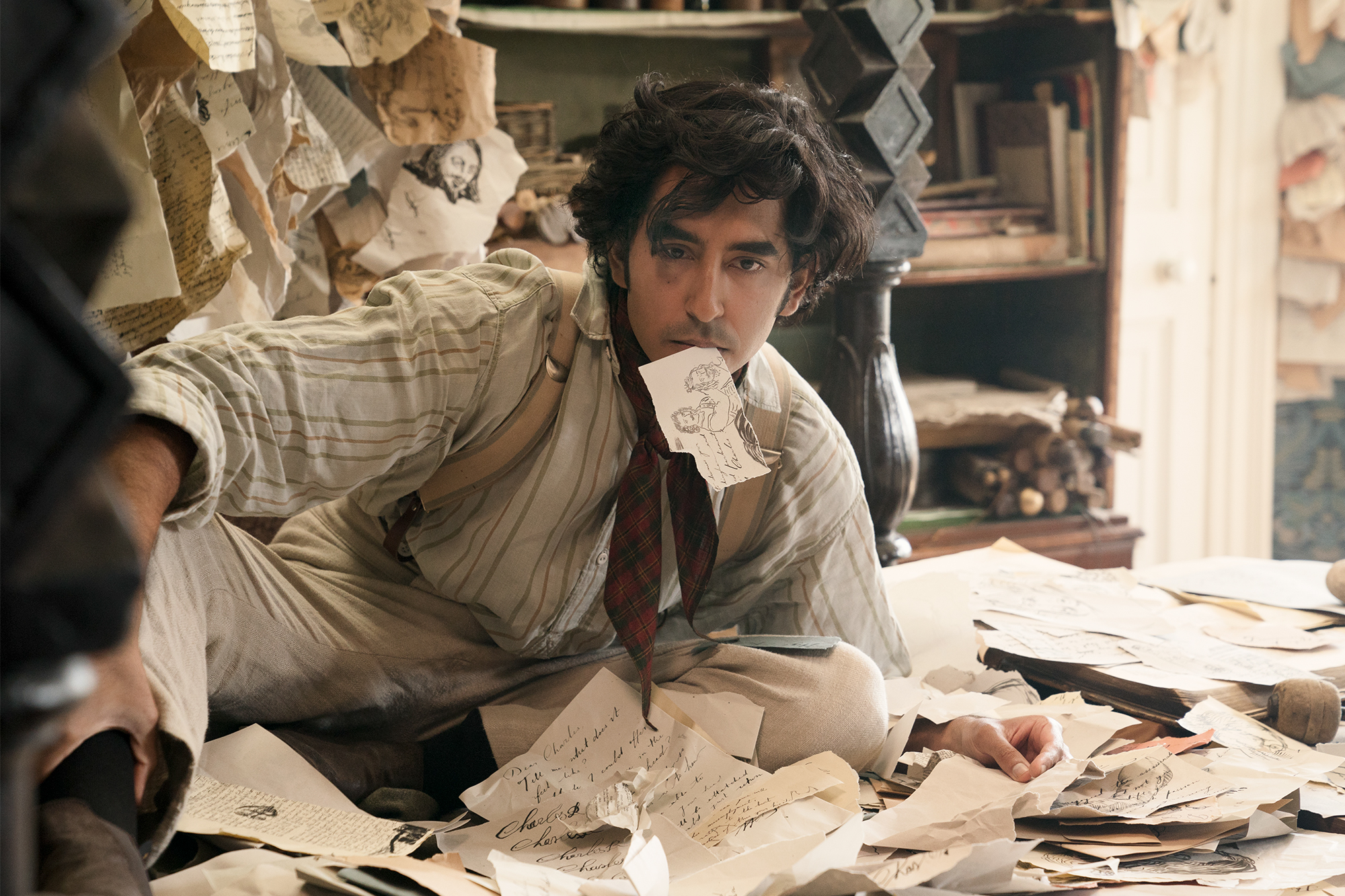 A young man sits in period garb, surrounded by papers.
