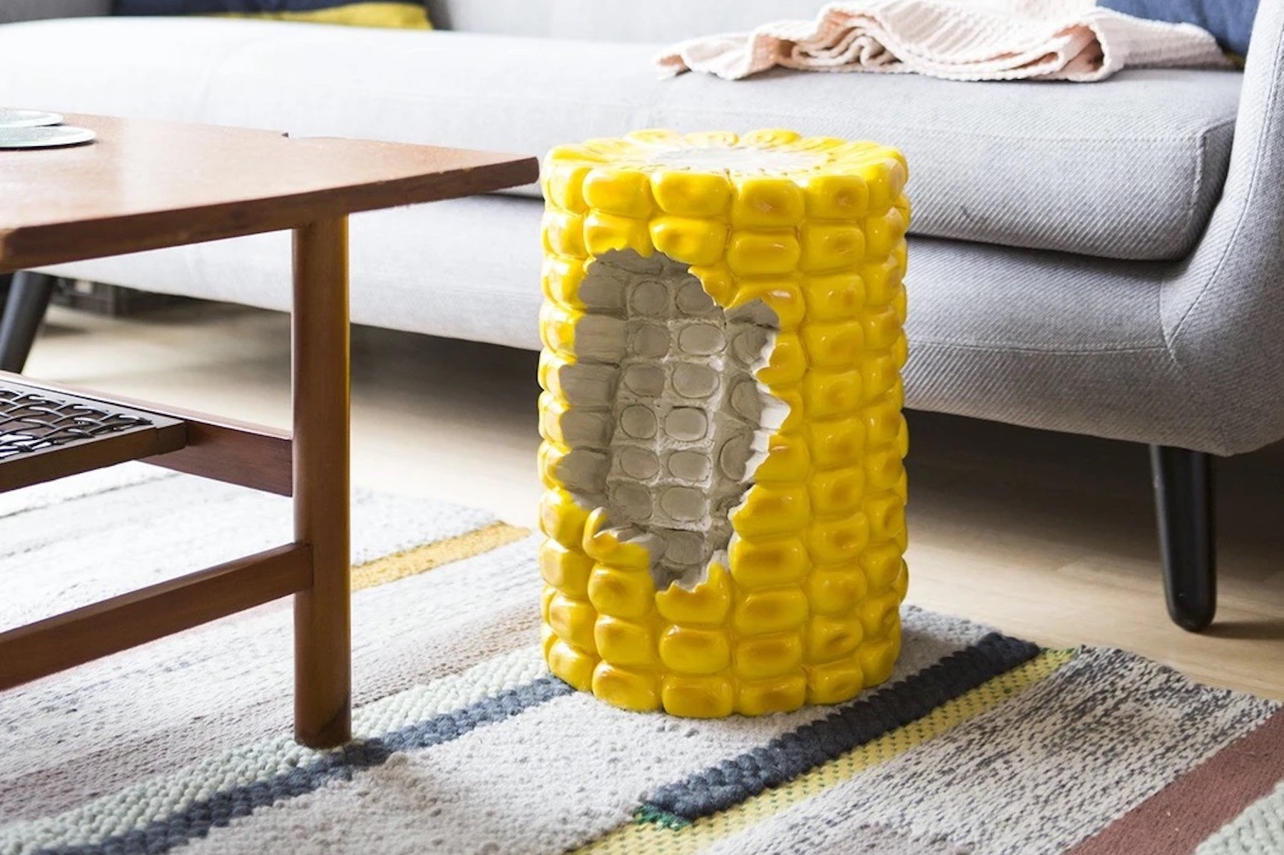 A stool shaped like corn-on-the-cob with a bite taken out of it is placed on a woven rug, next to a grey couch and dark wood coffee table.