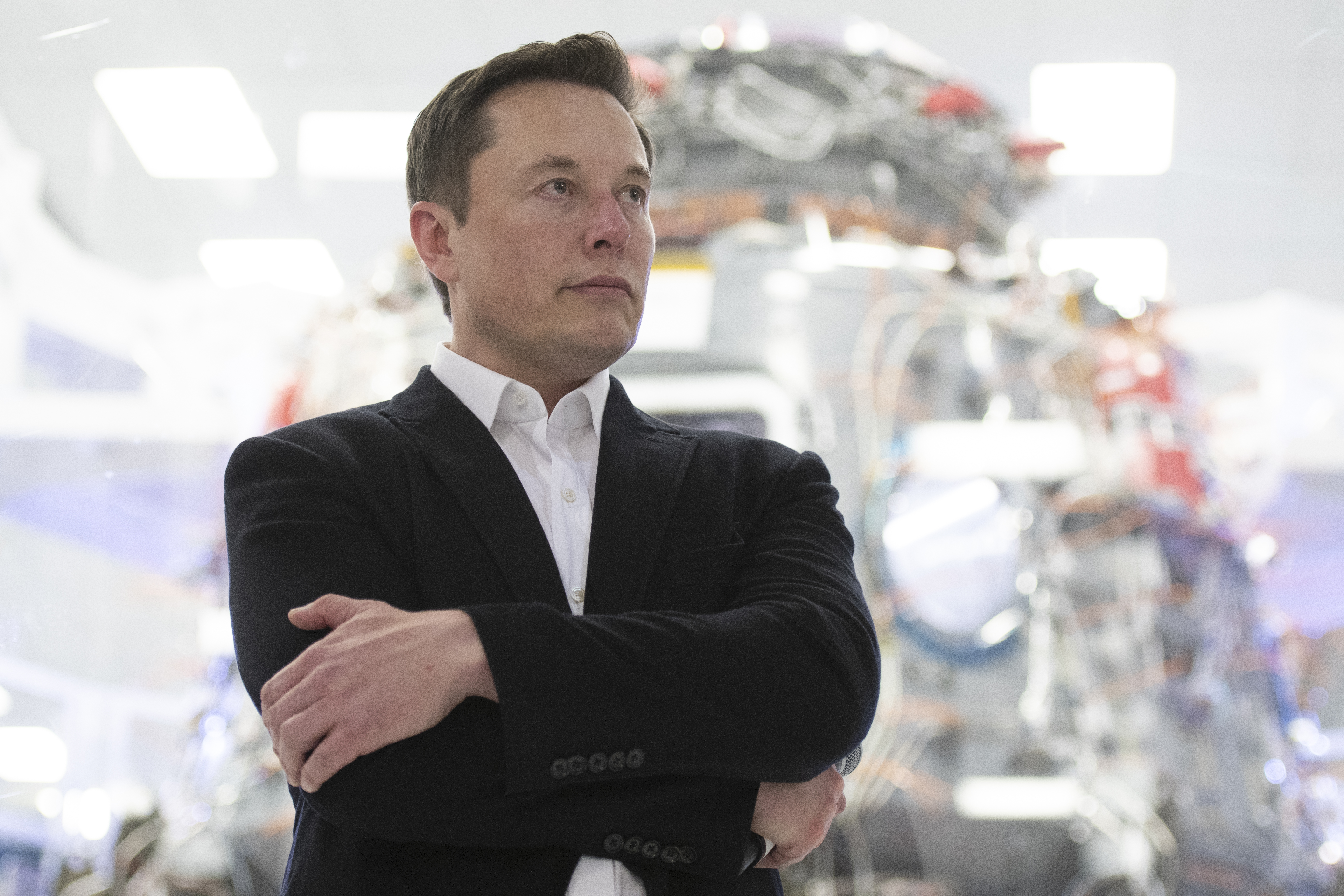 Elon Musk standing with arms crossed in front of a SpaceX capsule.