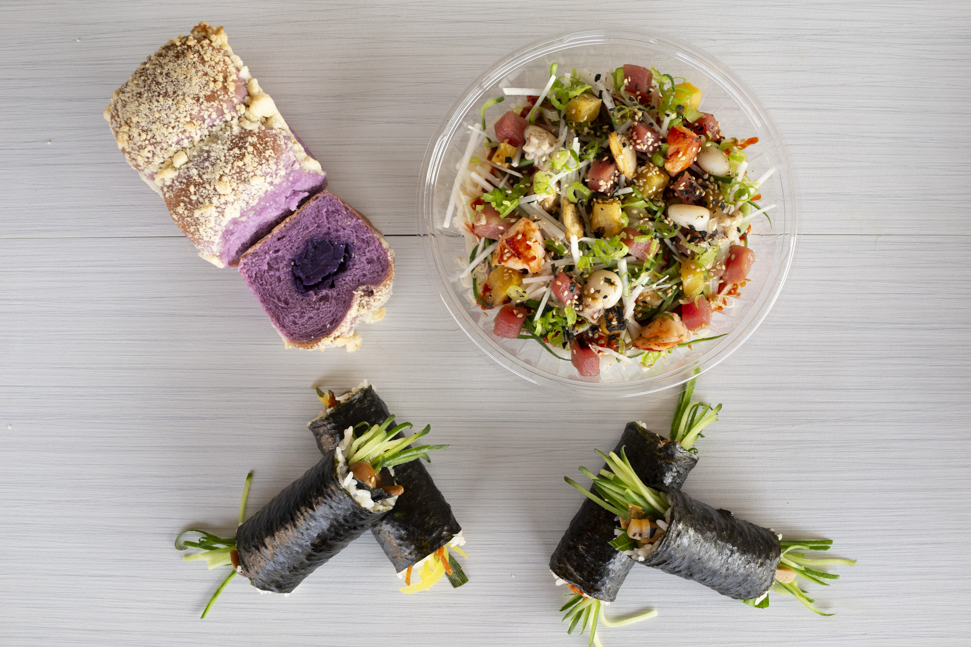 """An overhead spread of the """"Soboro"""" Ube Bread, four Bap rolls, and the Haemul Ssambap laid out on a white table"""