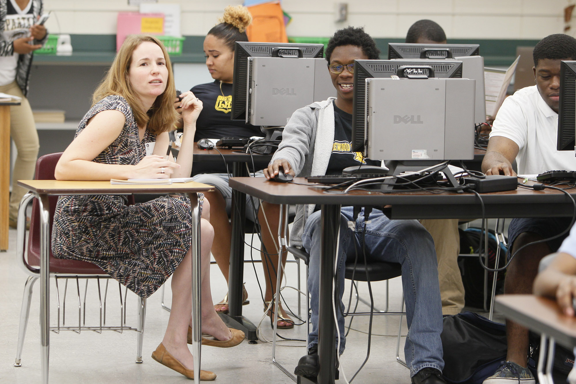 A reporter sits in a desk next to a student for an interview at a Florida high school in 2015.