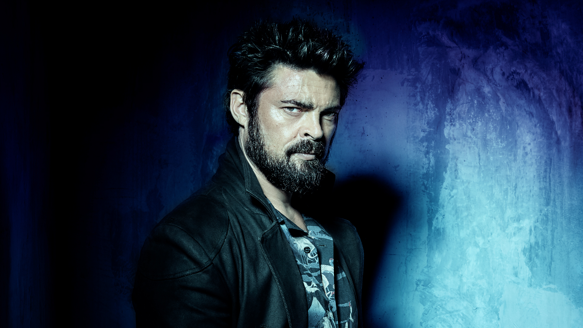 Man with beard scowling and looking to camera on a black and blue background