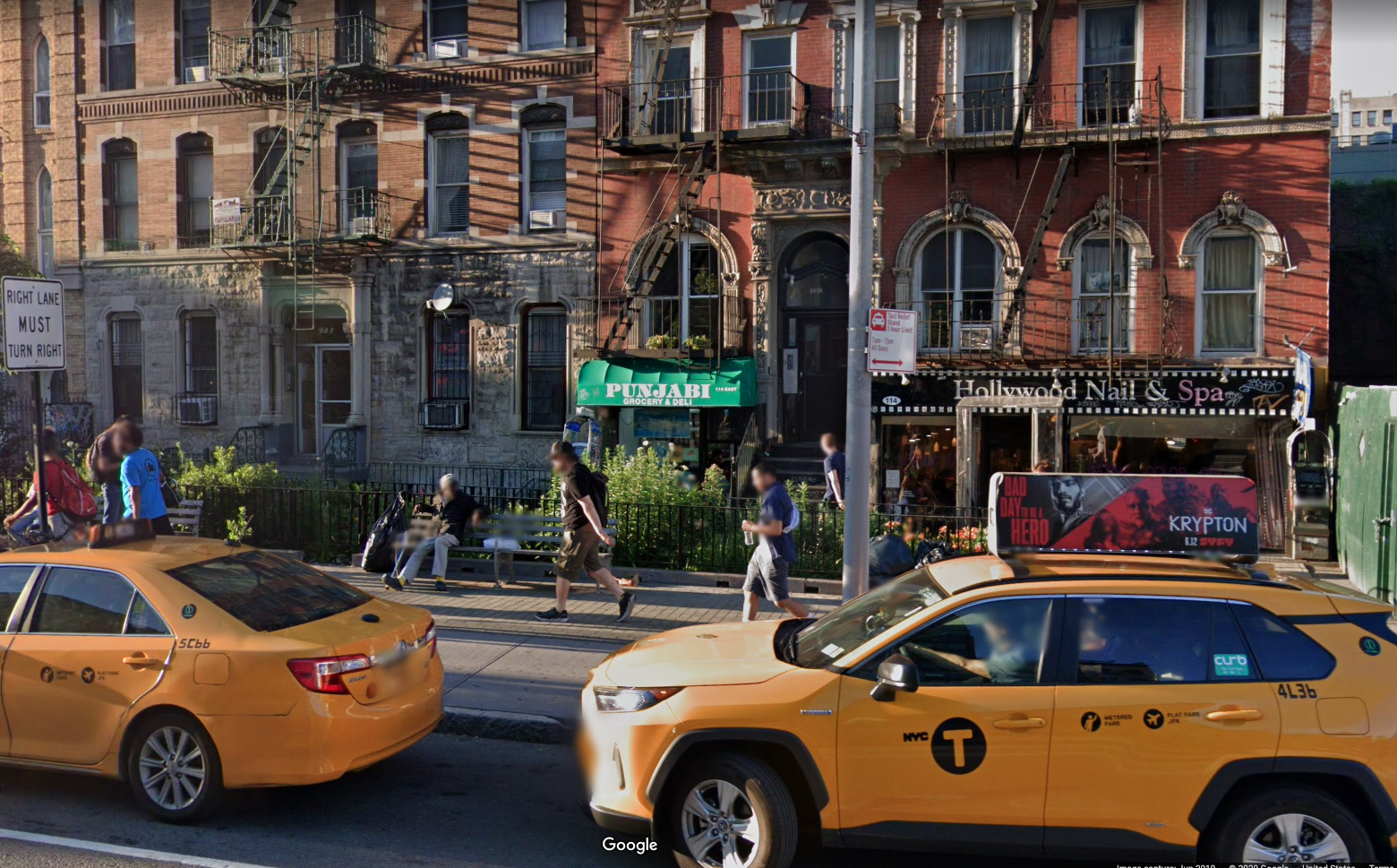 An exterior photo of the deli with a green awning out front and two yellow taxi cabs in the foreground