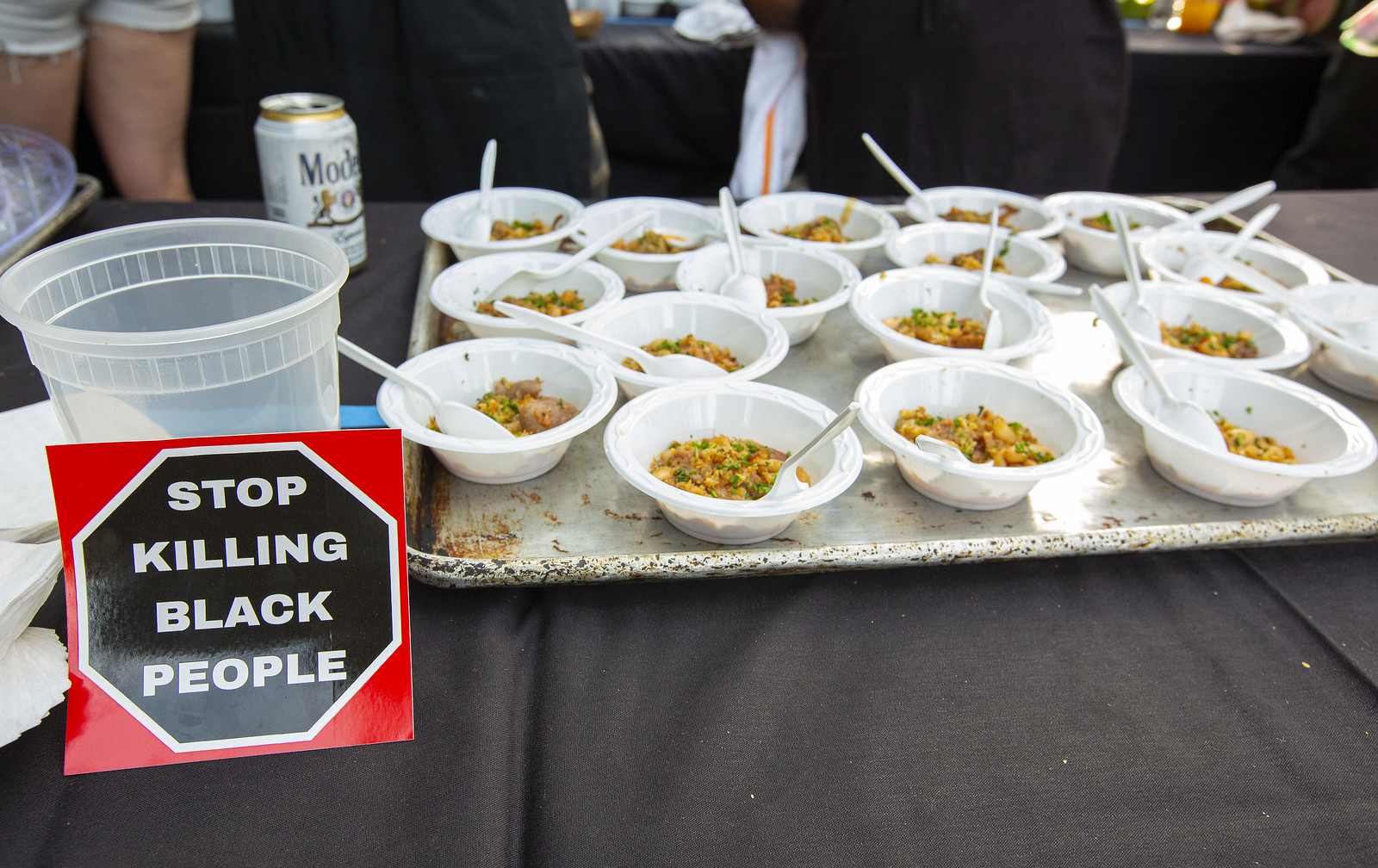 """A tray of food samples in plastic cups with a sign """"stop killing black people."""""""
