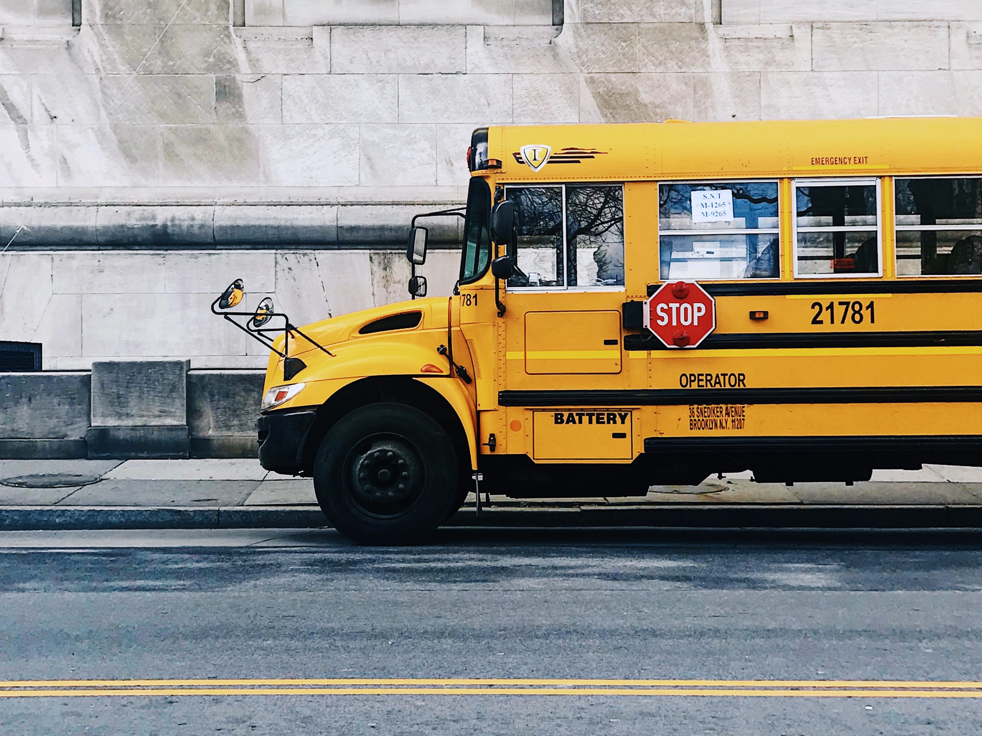 Yellow school bus driving along a city street.