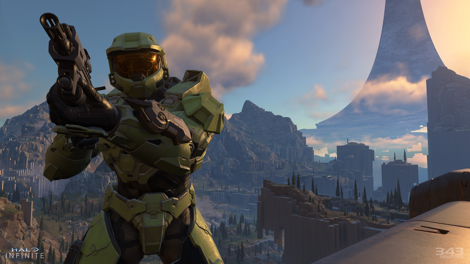 Master Chief aiming a gun while standing high up above a valley in Halo Infinite