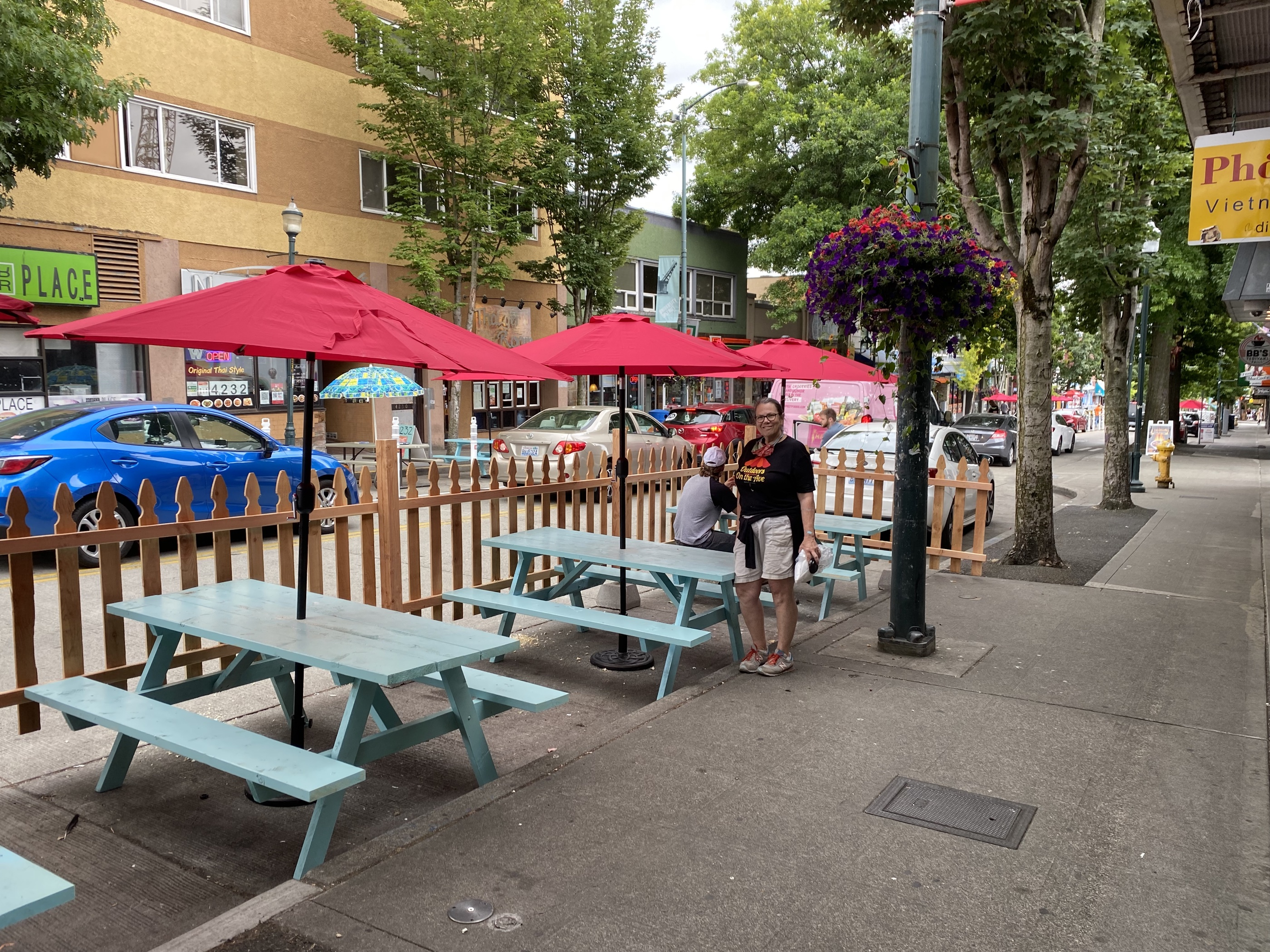 Light blue picnic tables surrounded by fencing and pink umbrellas on a city street