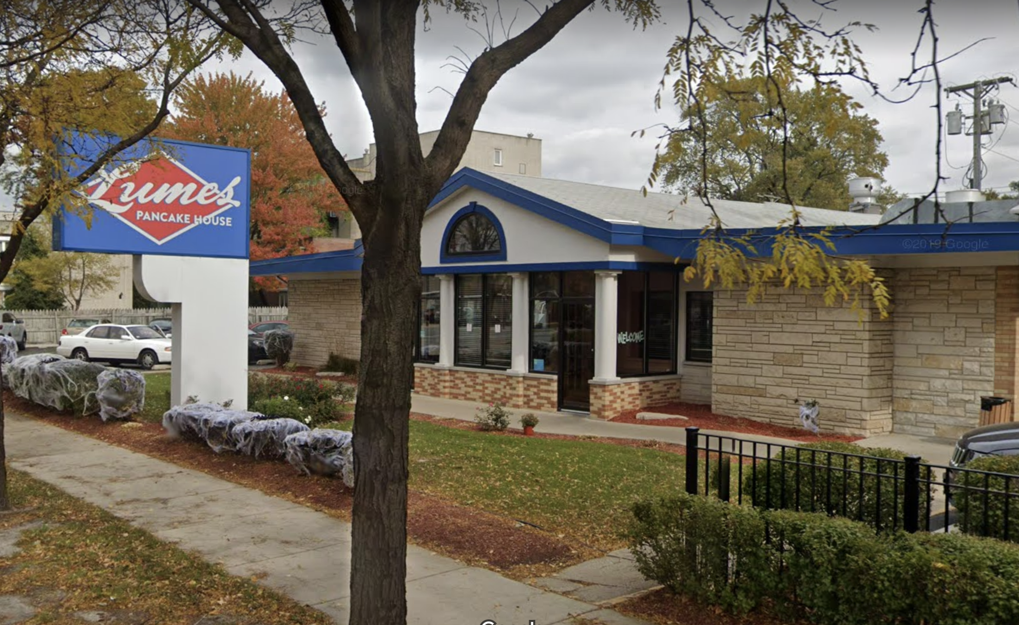 A large white and blue restaurant visible from the sidewalk.