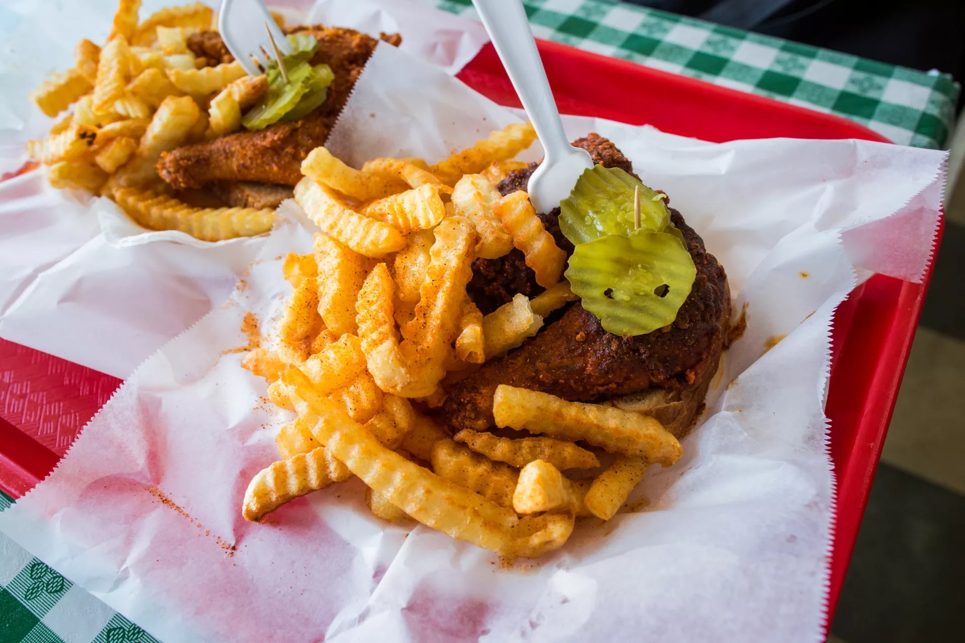 Hot chicken with crinkle cut fries and pickels on top