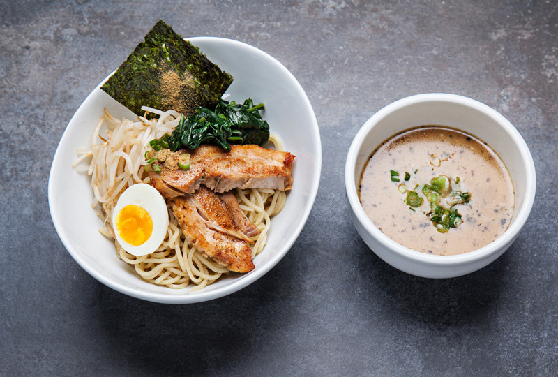A bowl of ramen stuffed with noodles and an egg on top, and a bowl of a beige-colored soup on the side