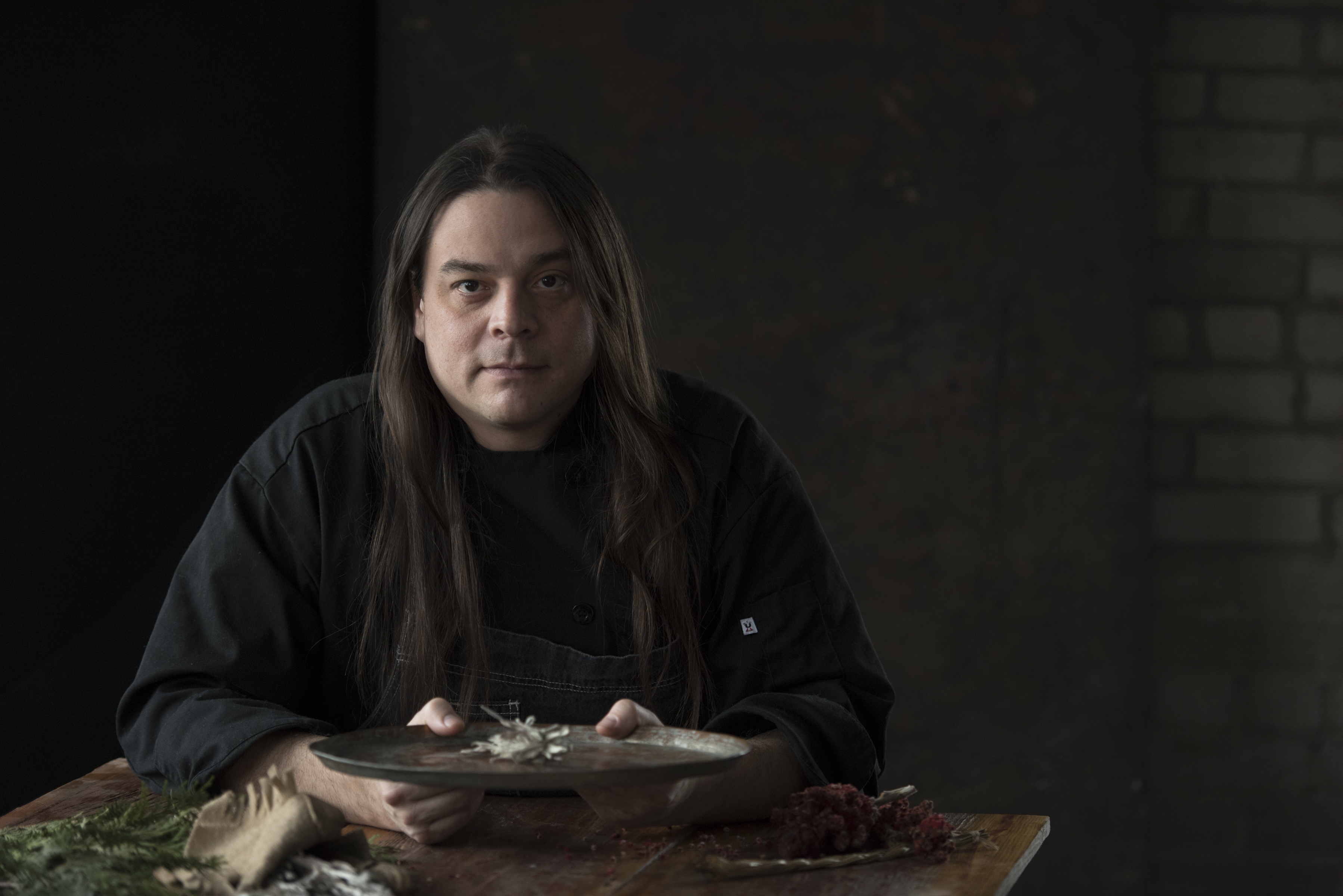 Man with long hair sitting behind table with a dark black background.