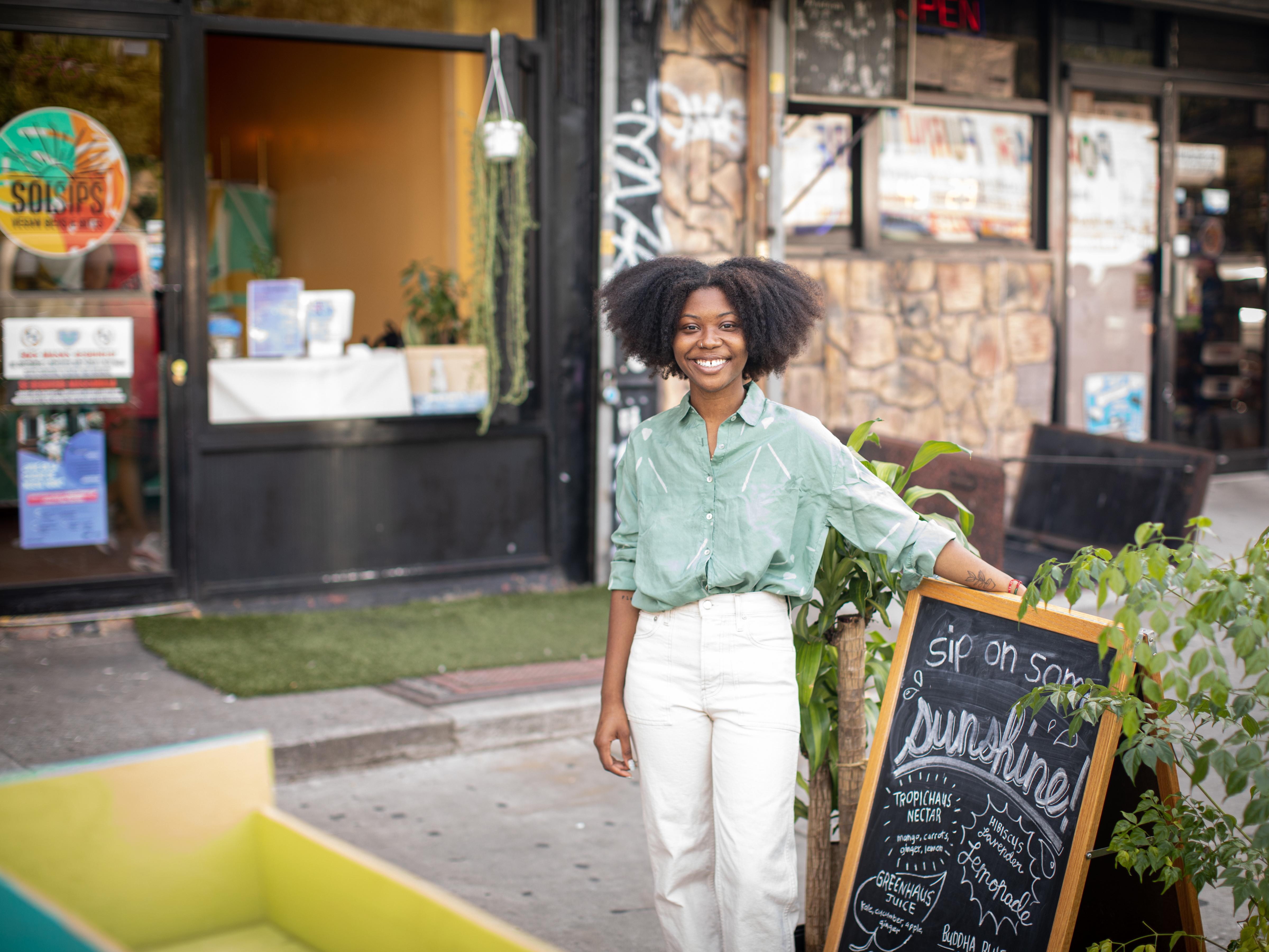 Smiling woman standing in front of a sandwich board.