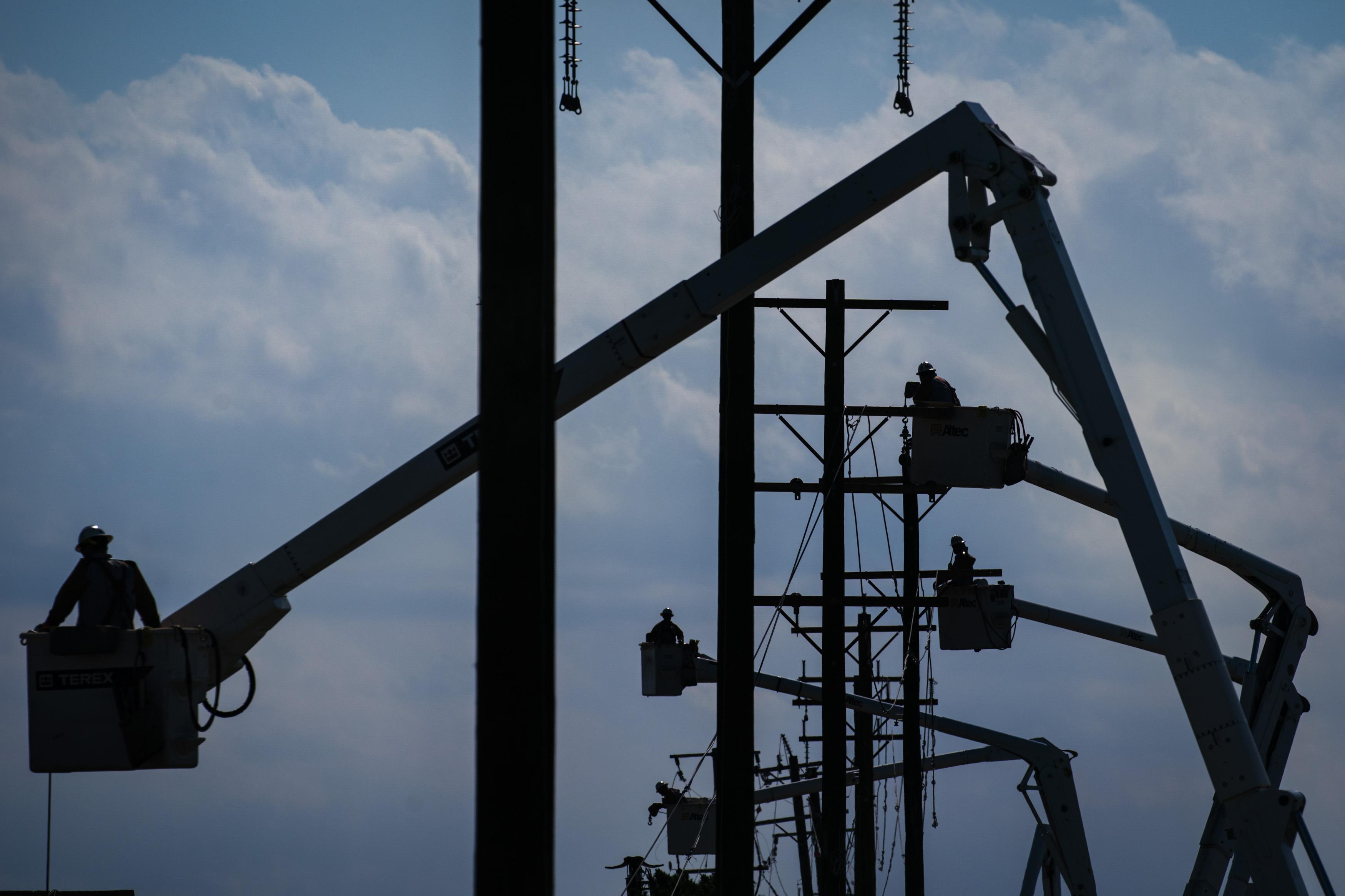 Utility workers repair power lines.