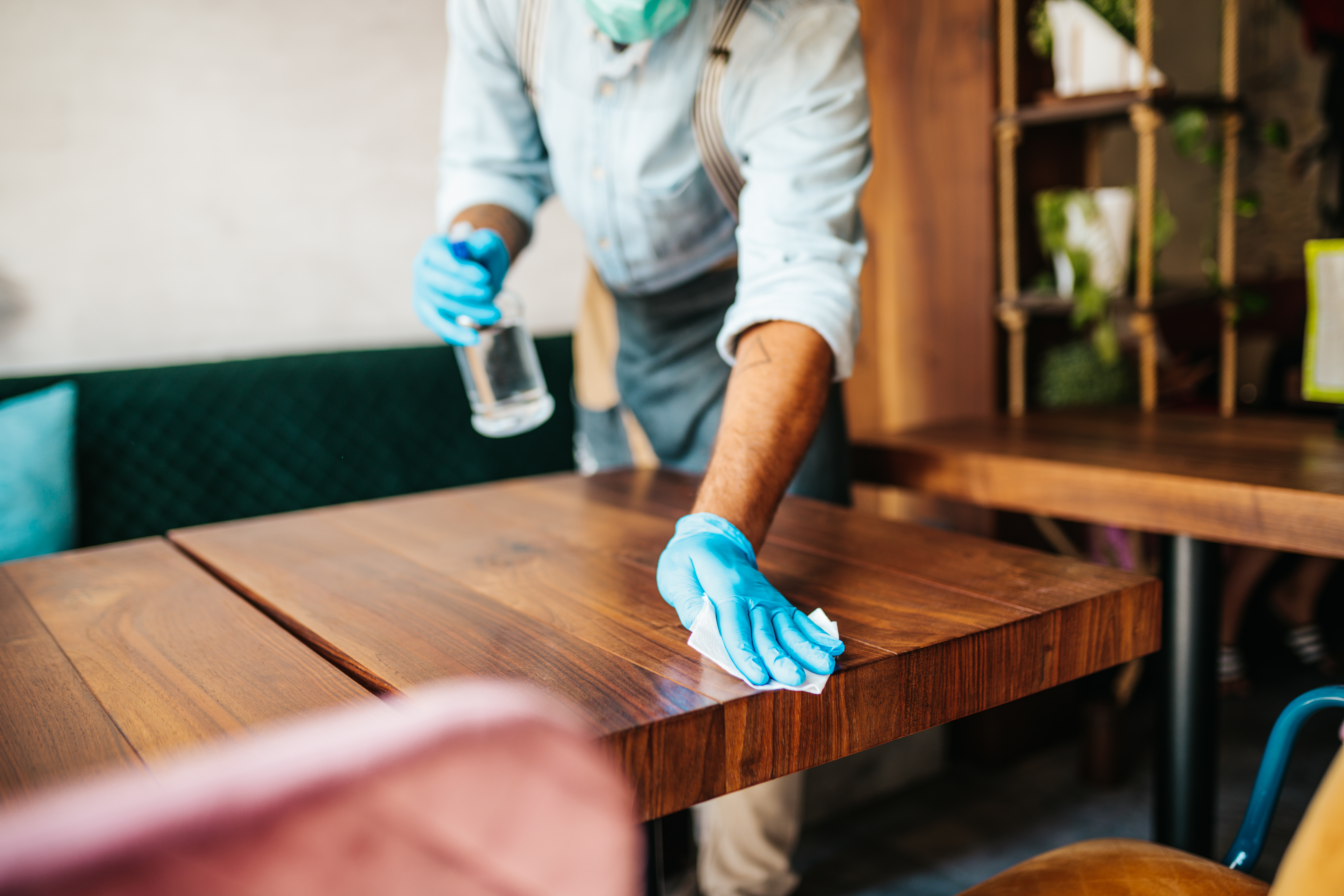 Waiter cleaning and disinfecting restaurant table for next customer. Corona virus and small business is open for work concept.