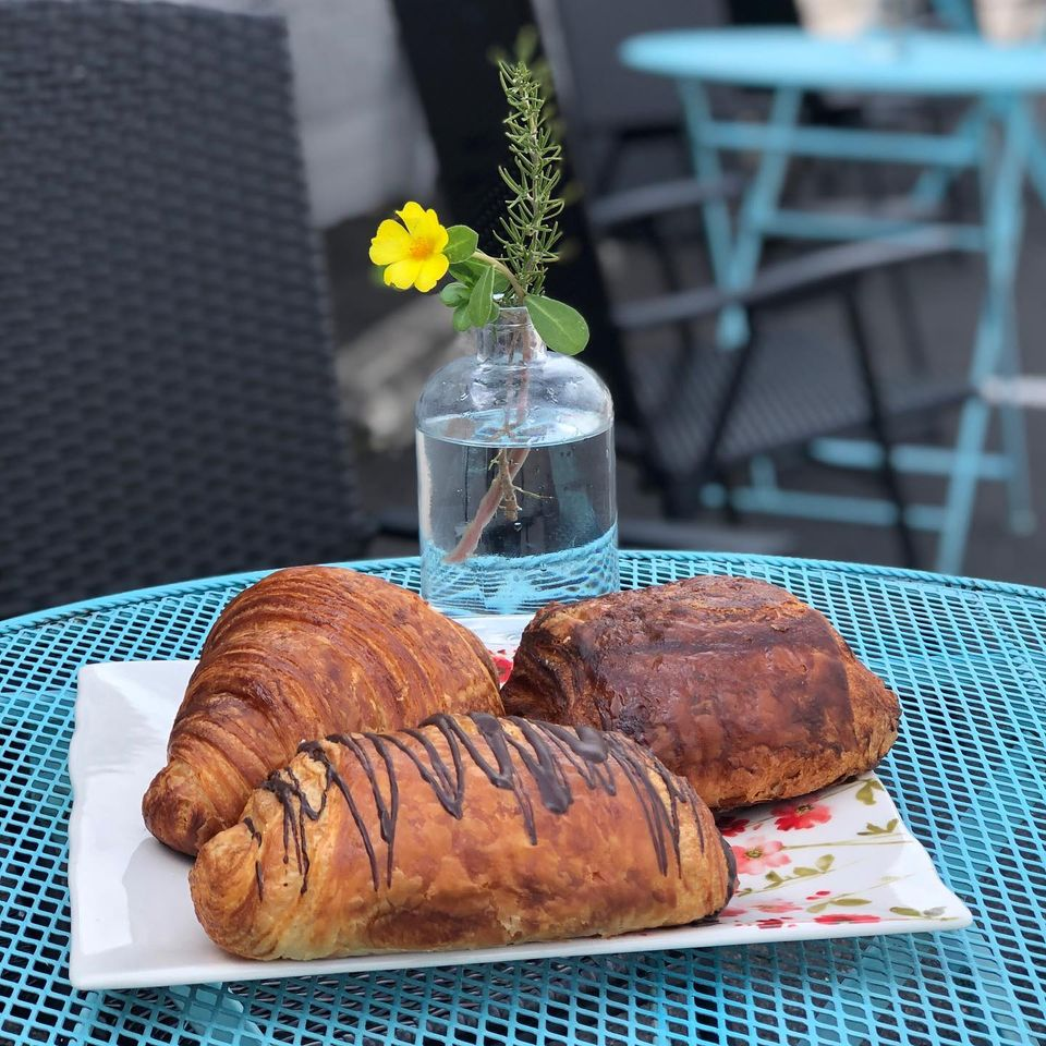 A regular, chocolate, and some other kind of croissant on a blue metal table with a yellow flower in a vase in the background.