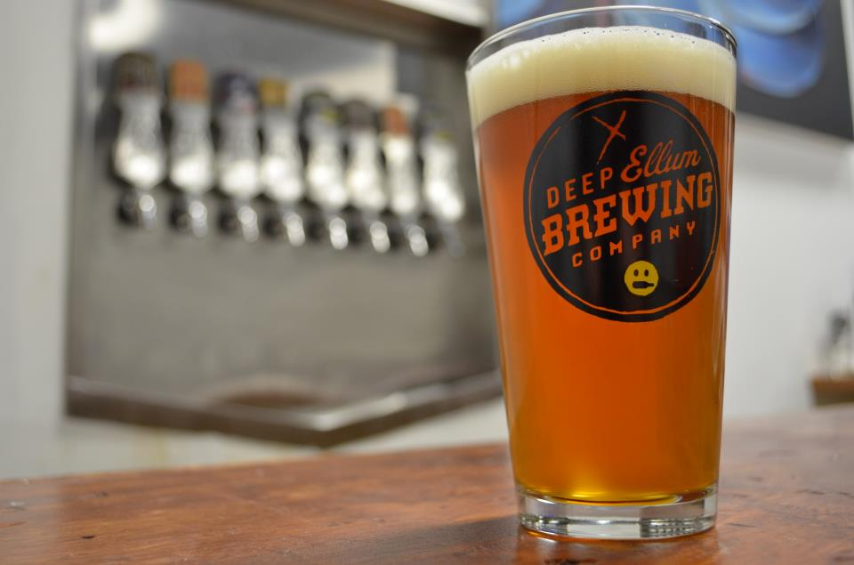 """A pint of beer in a clear glass with a """"Deep Ellum Brewing Company"""" logo. A wall of beer taps is in the background."""