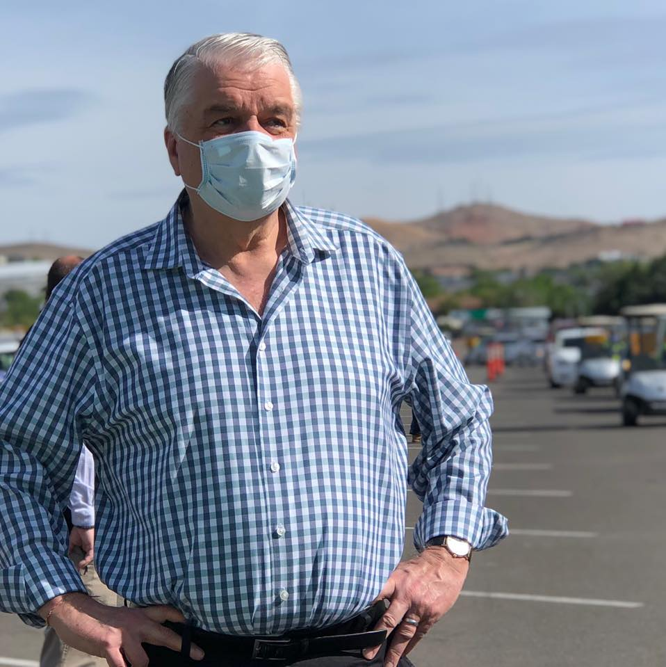 A man with gray hair wears a mask and a blue checked shirt.