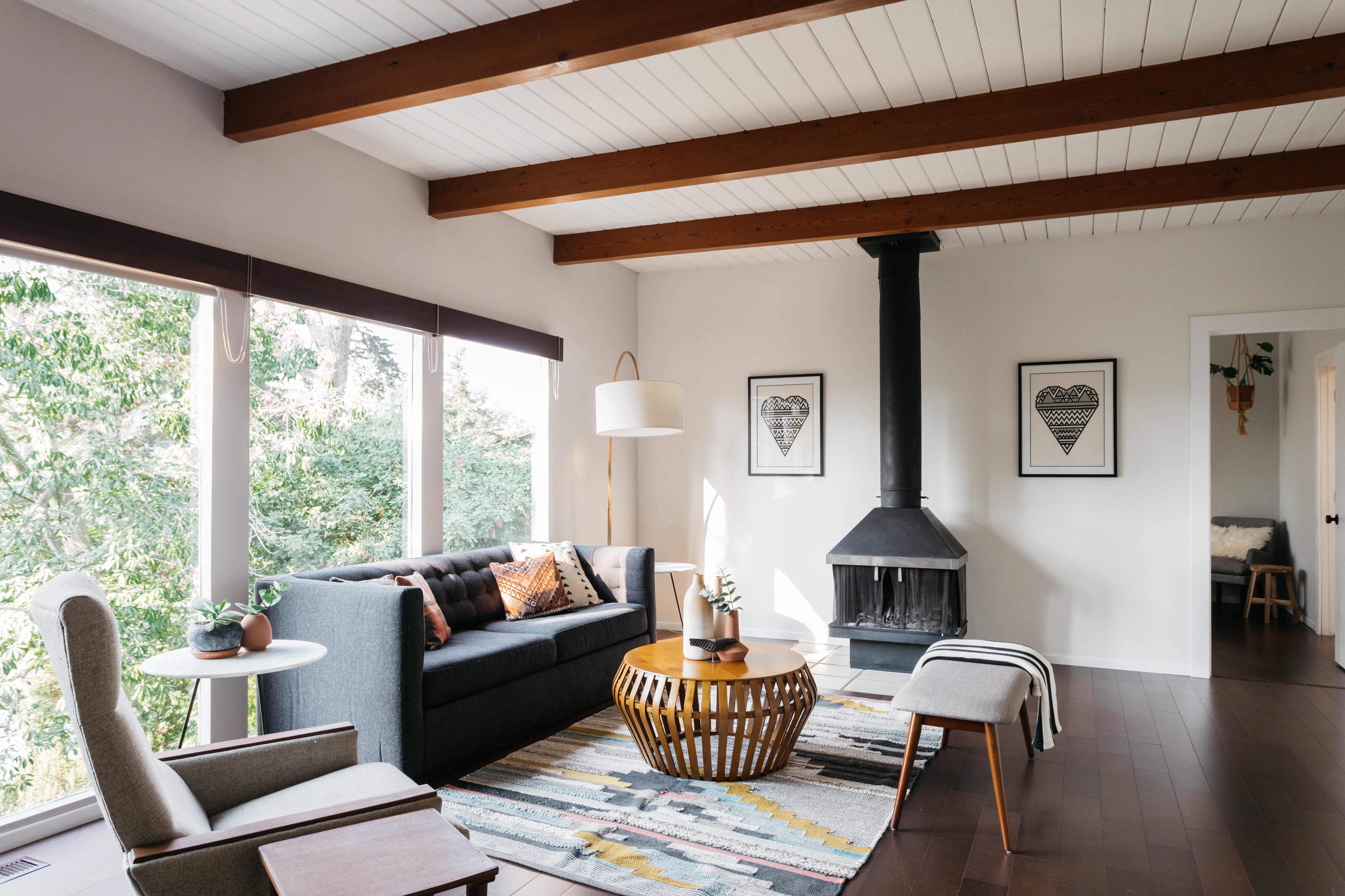 Bright room with wood beam ceilings, glass walls overlooking trees, and a black fireplace.