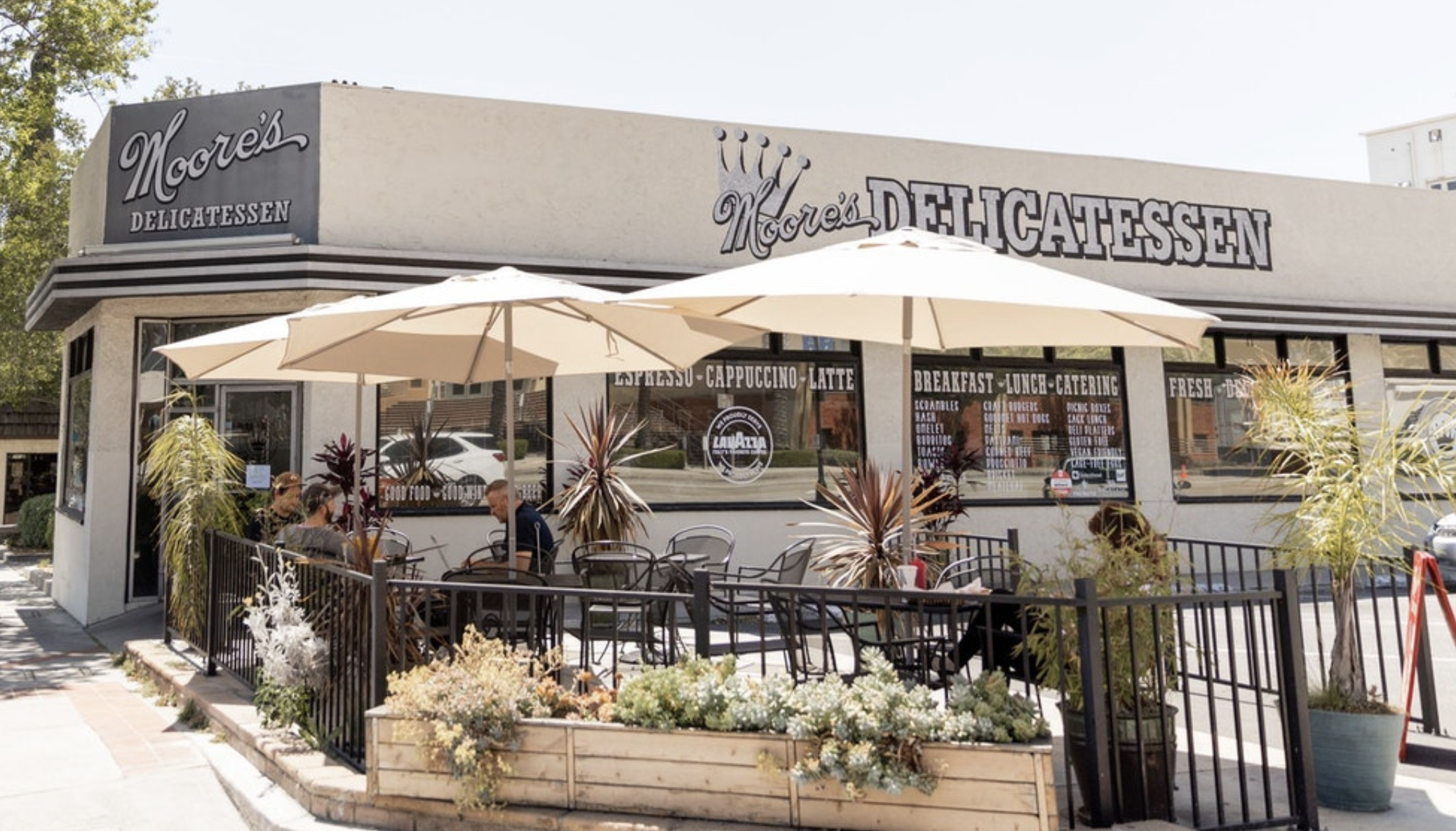The exterior of a grey and tan deli restaurant with patio seating in the sun.