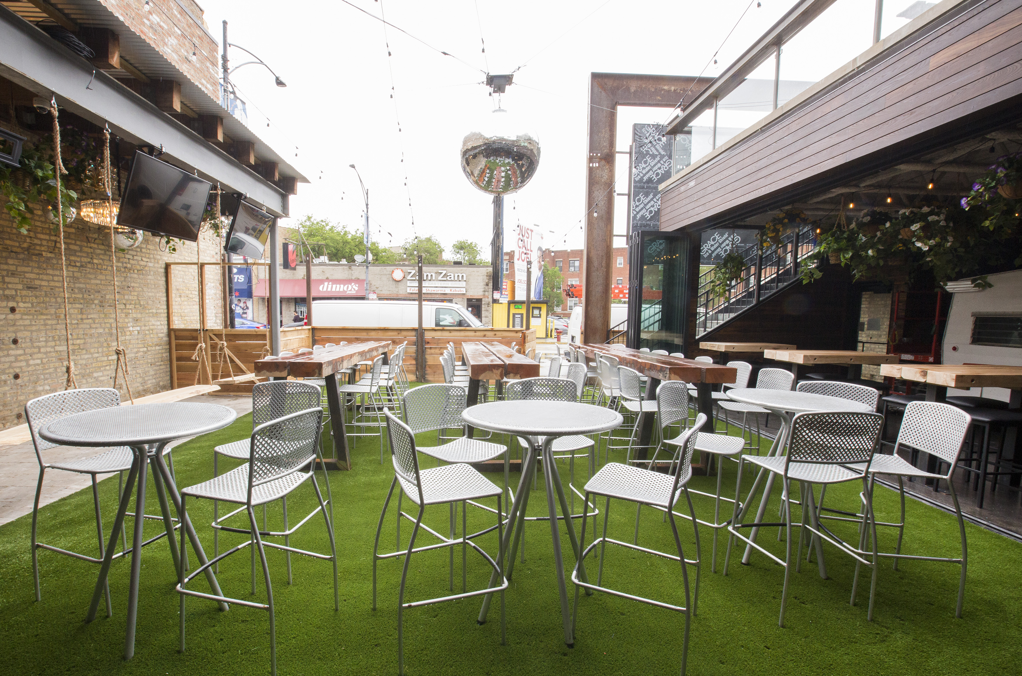A patio with several metal tables and chairs standing on artificial green turf.