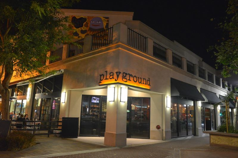 Outside of Playground, Downtown Santa Ana with signage and dim spot lighting.