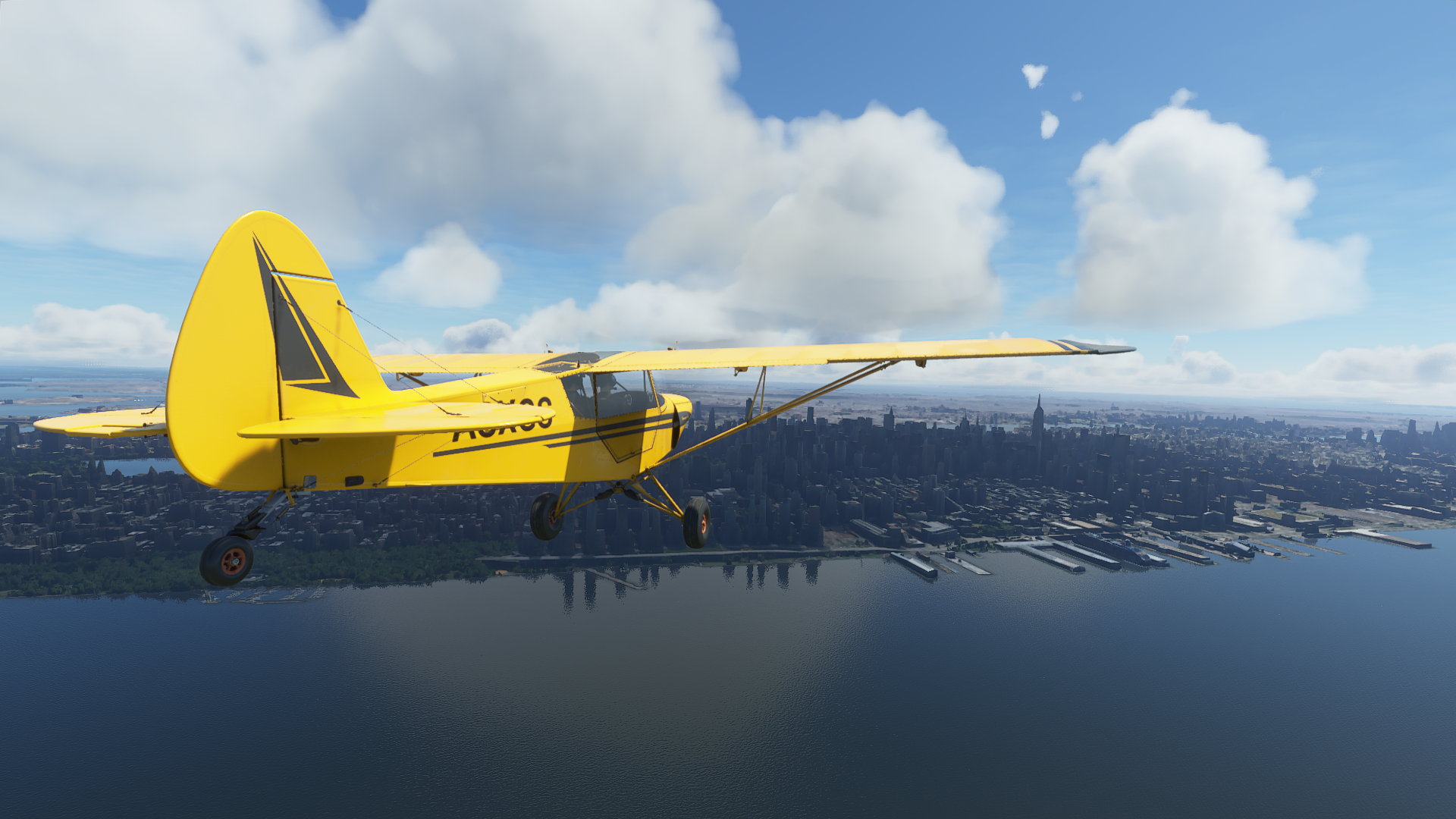 A yellow plane flies over the cloudy skies over New York City