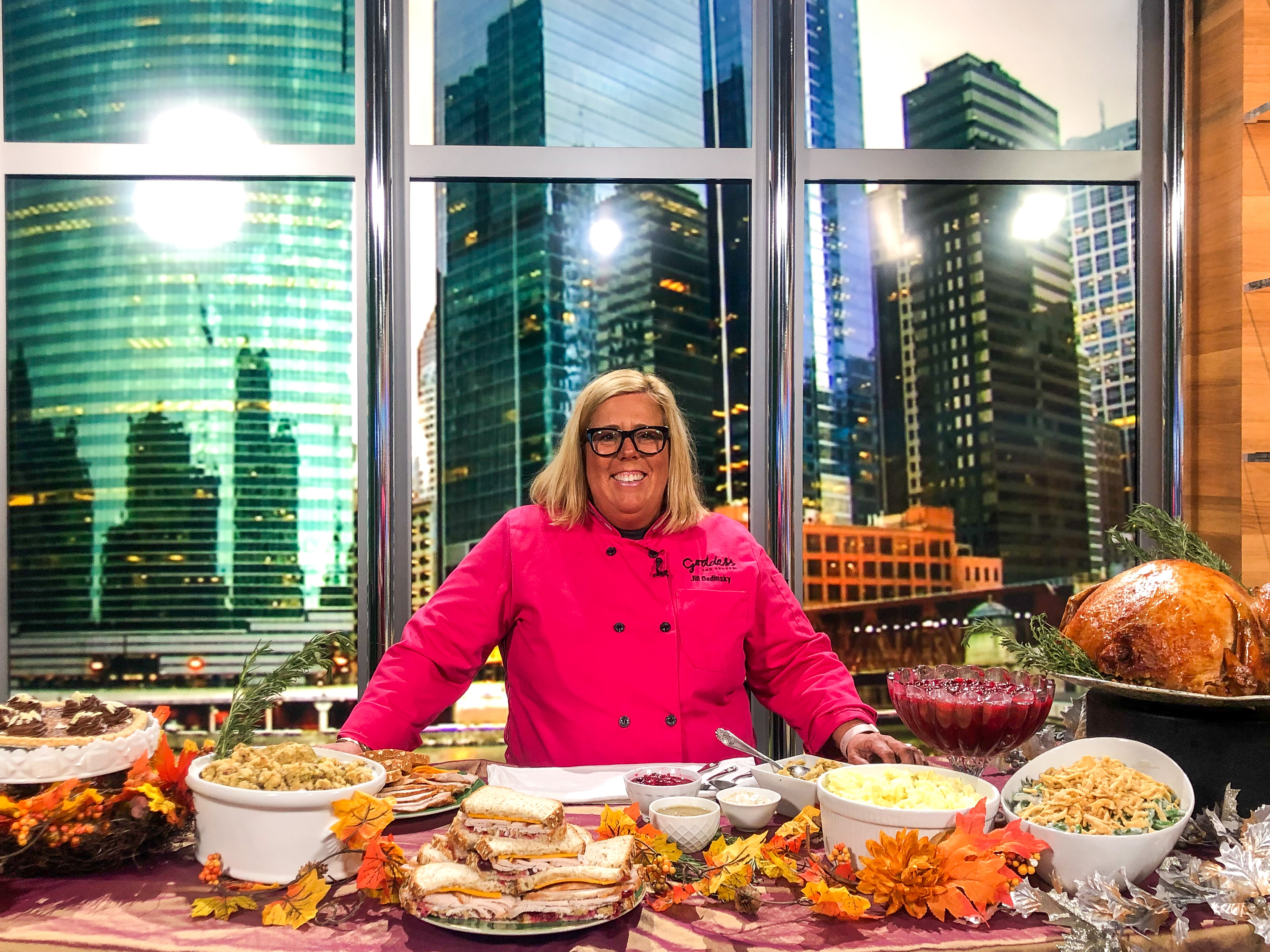 A woman with blonde hair and a bright pink chef's coat stands smiling behind a table full of ingredients.