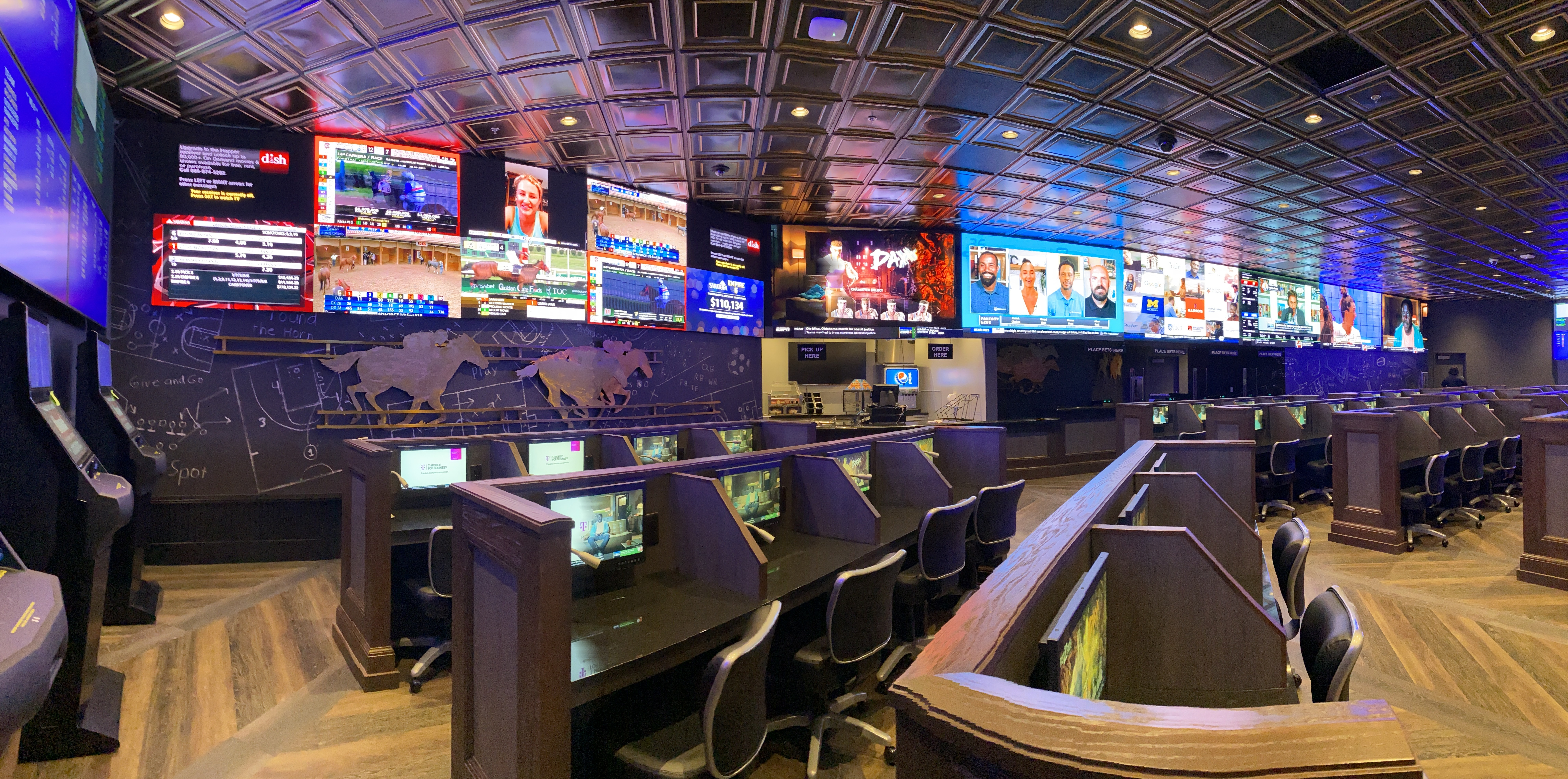 A wall of video screens with individual desk areas