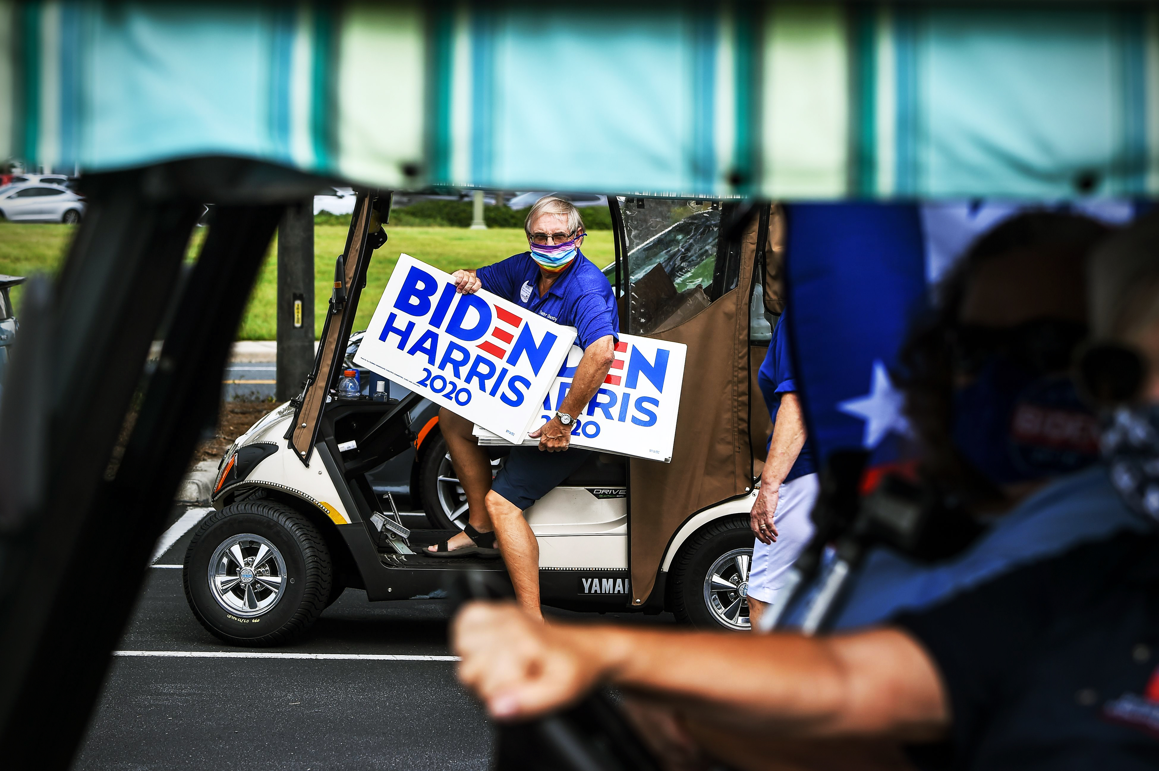 "A man in a golf cart with signs reading ""Biden/Harris 2020."""