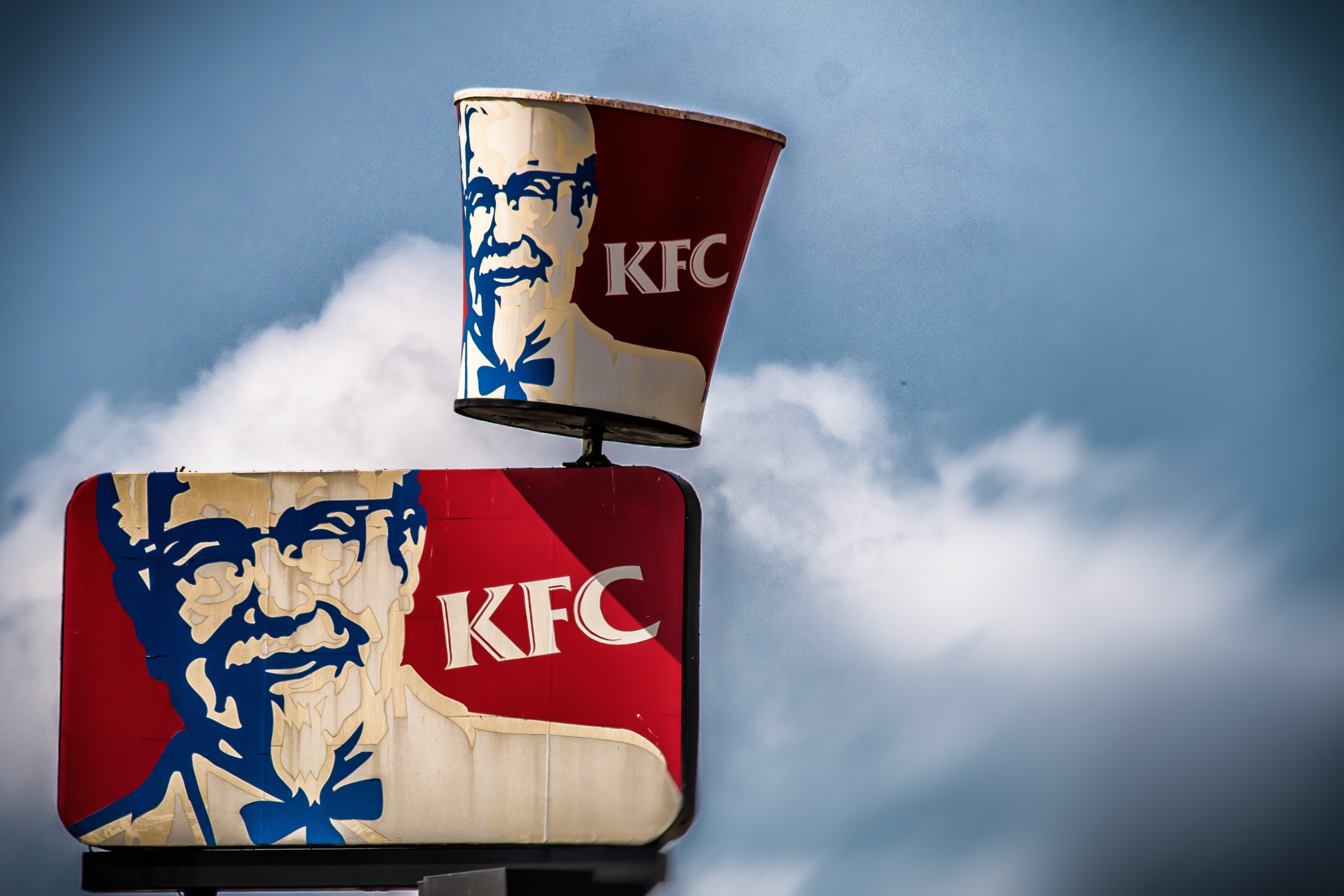 A sign for KFC against a clouded sky