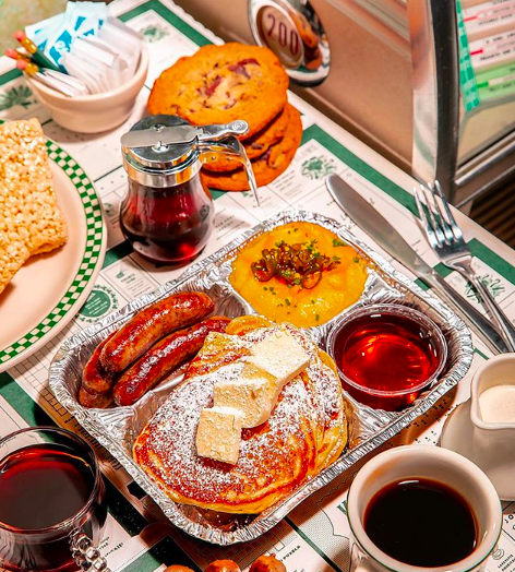 A metal tray with pancakes and butter, a pile of sausage, syrup, and sweet potatoes.