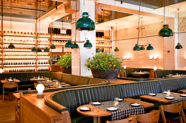 interior of restaurant with light wood booths and tables, black and white checked tablecloths, hanging green lights, and plants