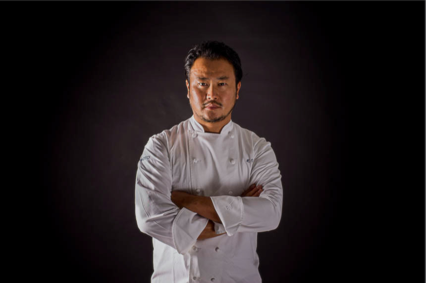 A chef named Makoto Okuwa stands with arms crossed against a black background.