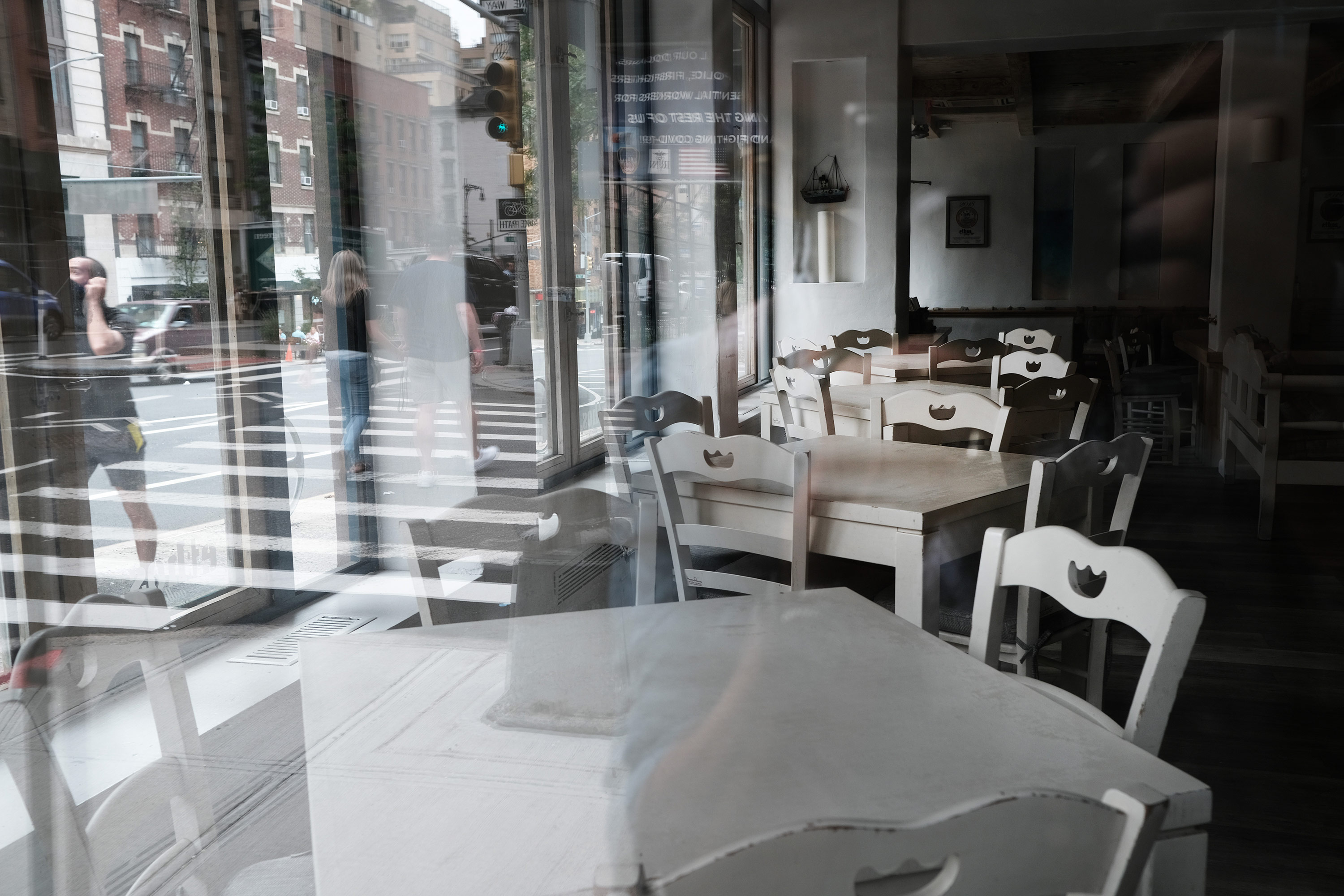 A row of white chairs and tables in an empty restaurant are facing a window looking out into a Manhattan street.