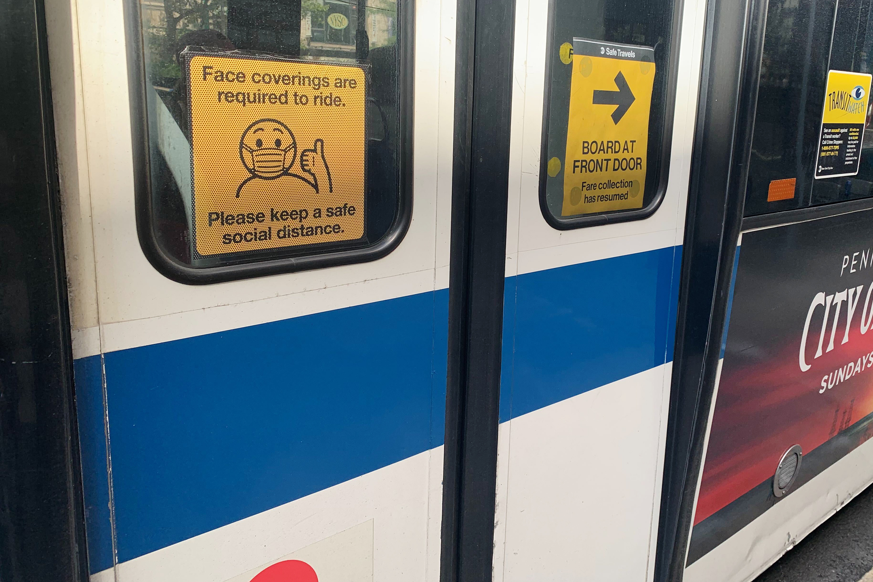 Exterior signs on MTA buses indicate new covid related rules