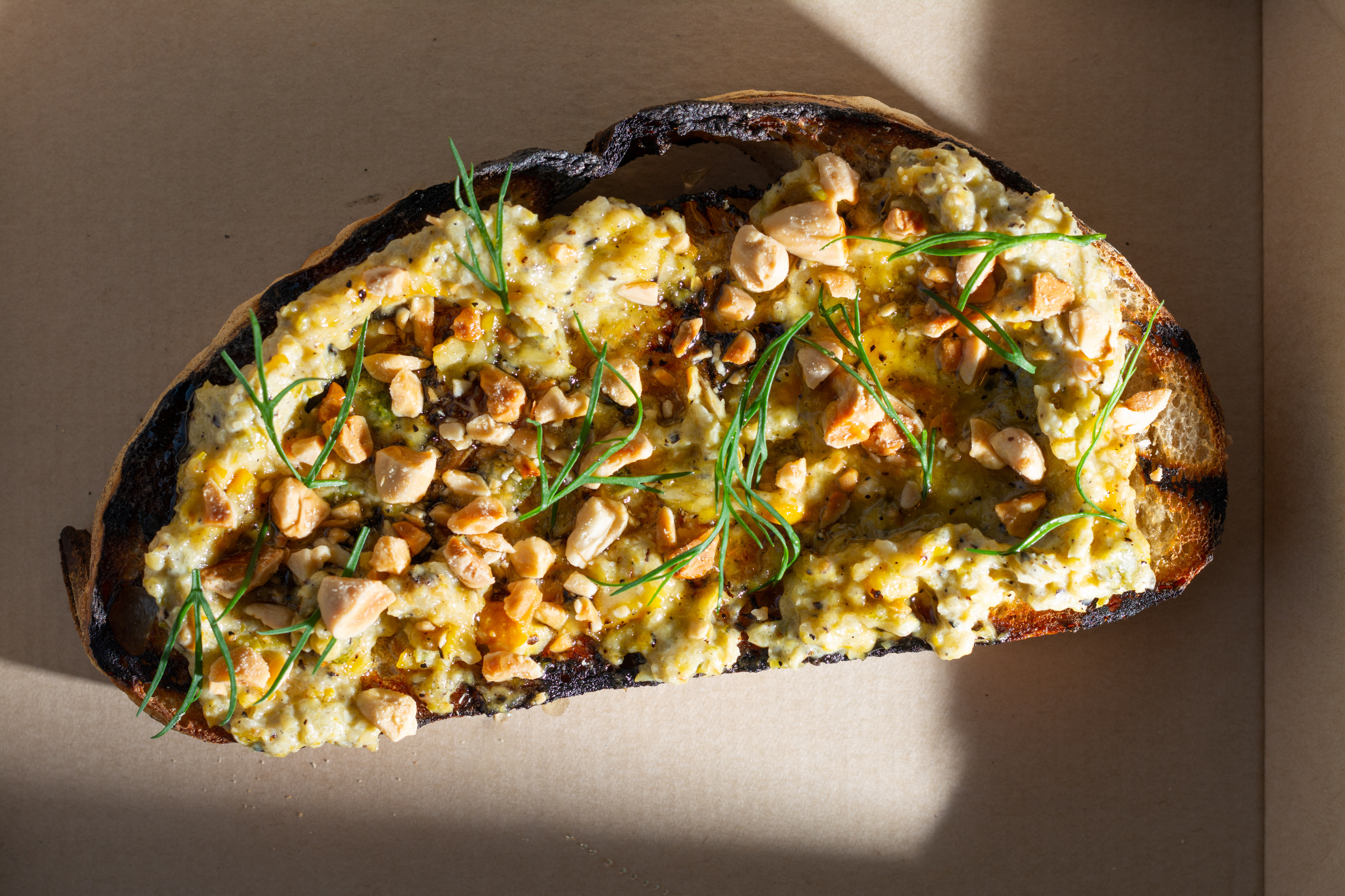 toast with mushed squash and and chopped almonds