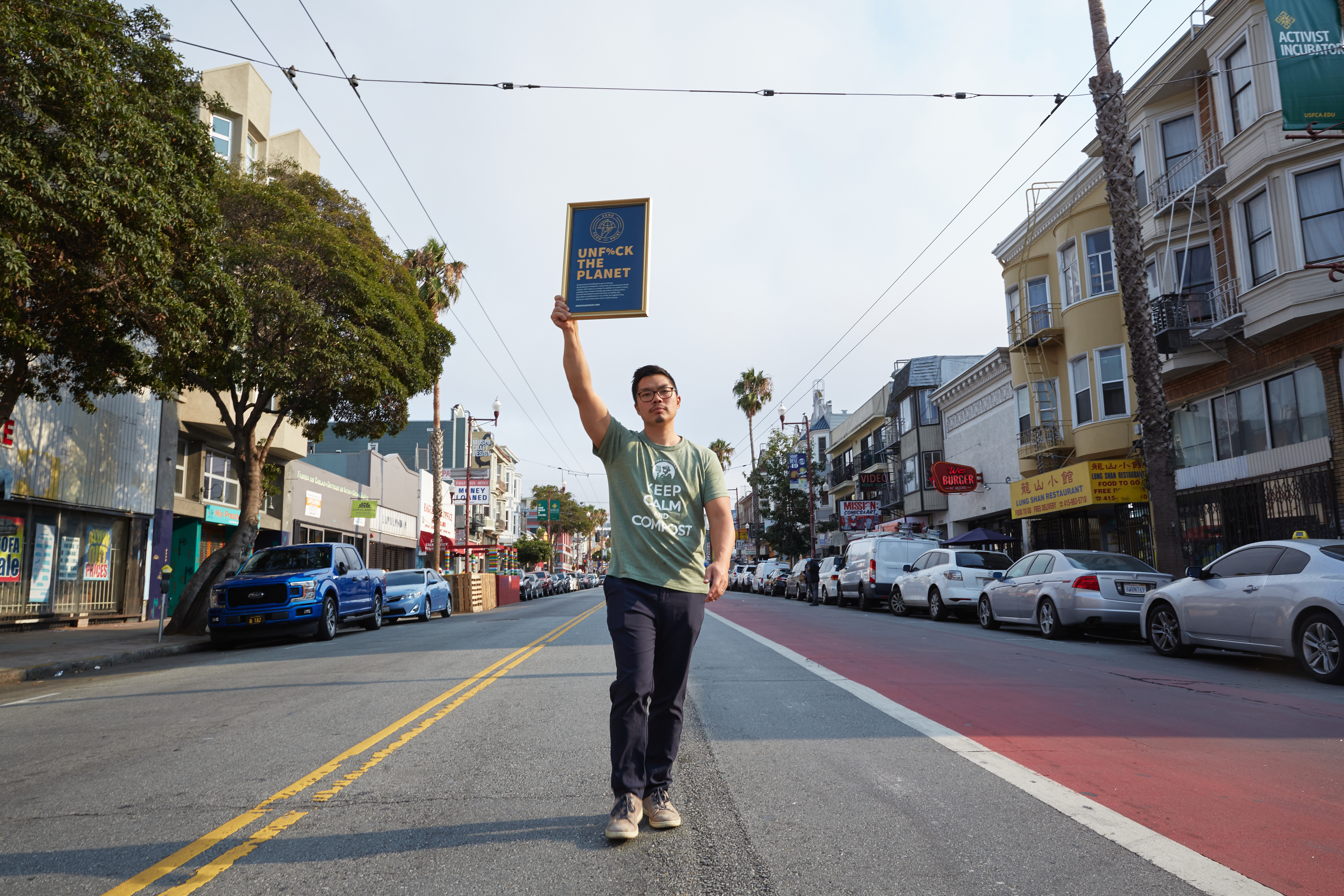 """Man wearing t-shirt that says """"Keep Calm and Compost"""" holds up a sign that says """"Unfu%k the Planet"""" standing in the middle of the street."""