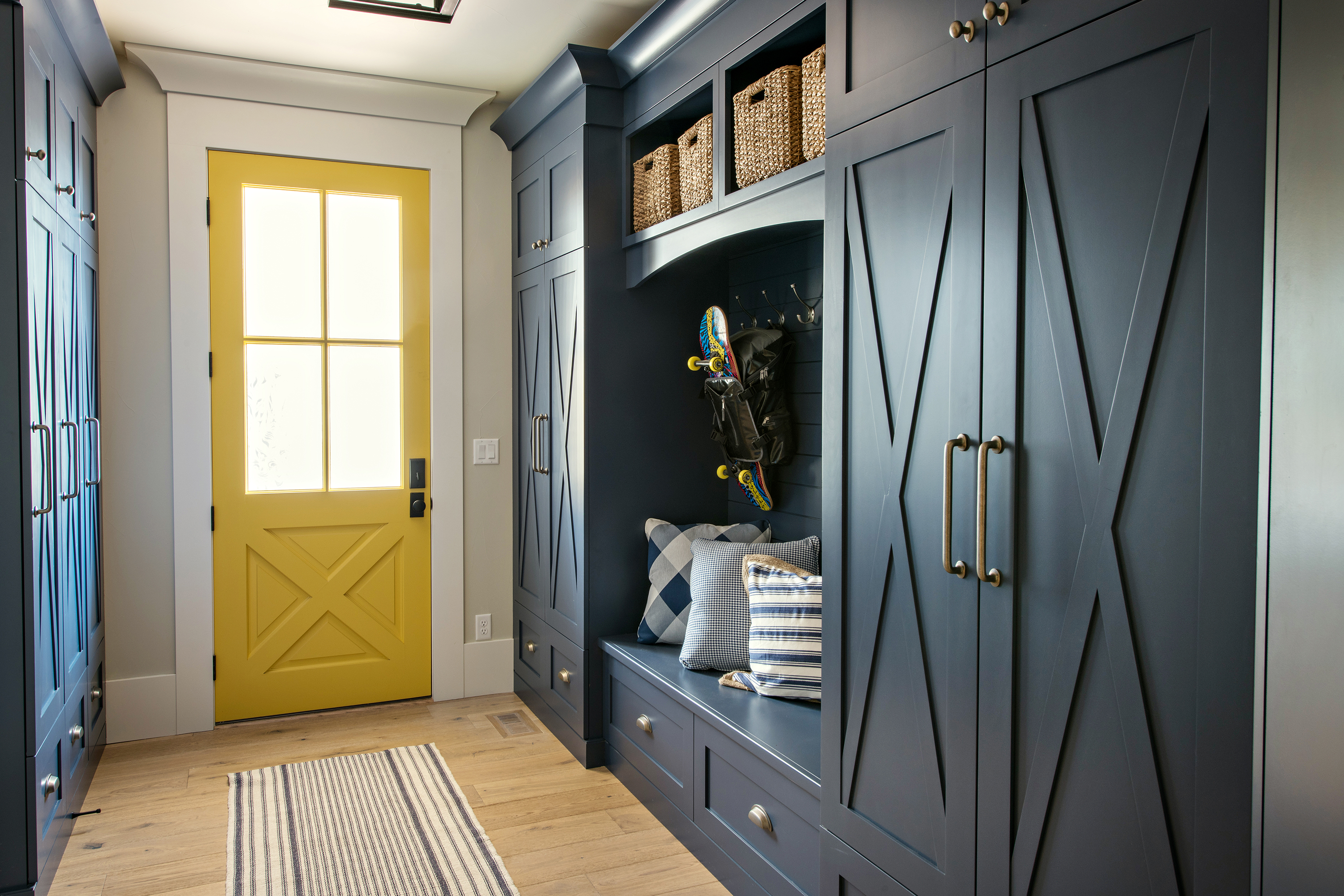 Mudroom with built in cabinets and storage with a yellow door.