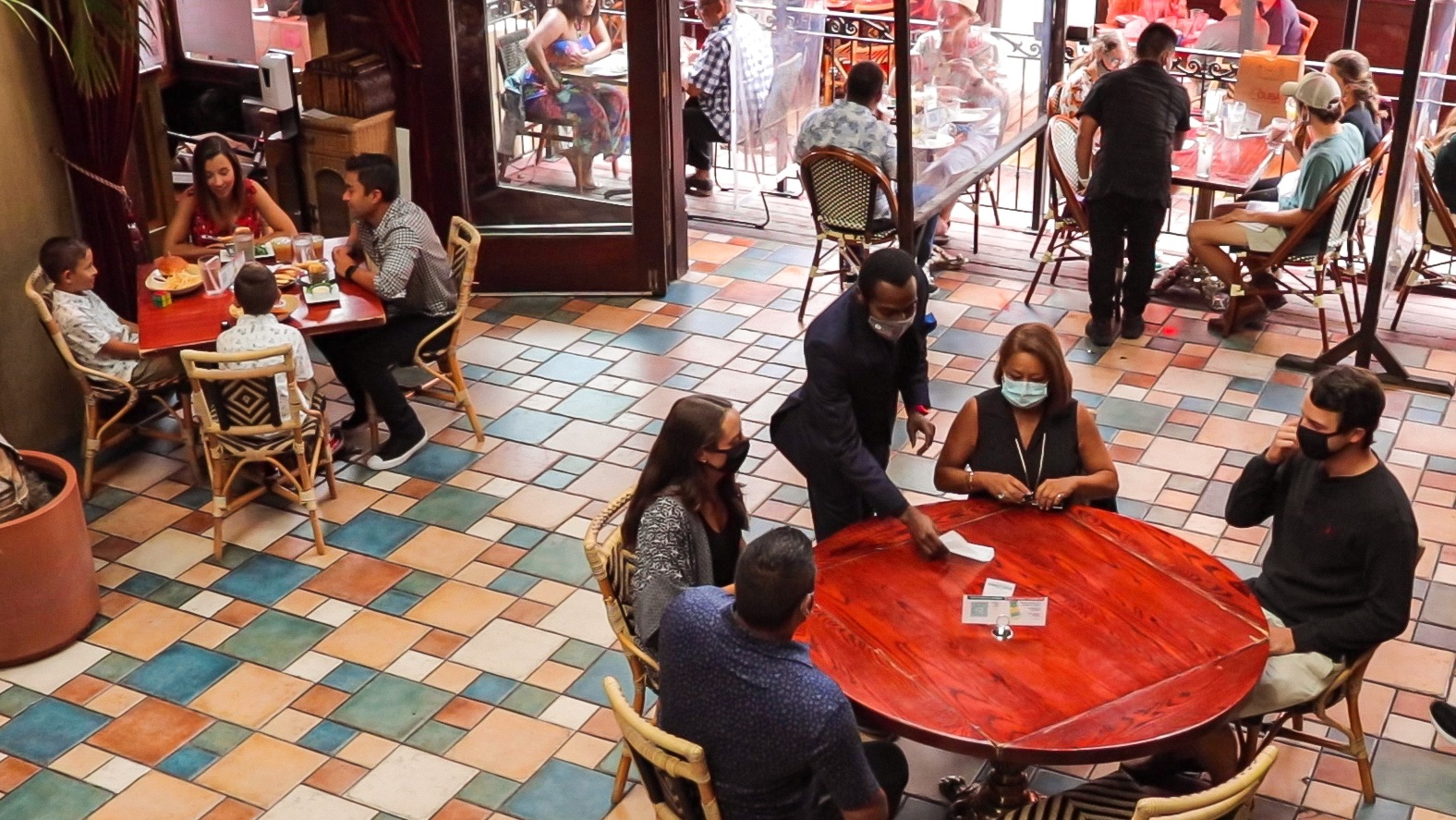 interior of restaurant with colorful tile floor, tables spaced apart, and diners and servers wearing pandemic face masks, with a view of tables outside